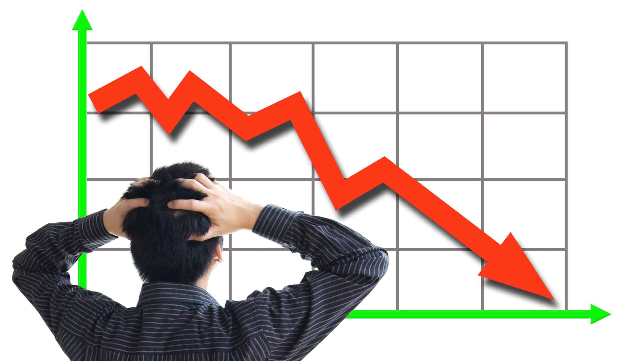 man with hands on head looking at chart with red downward arrow, stock market crash