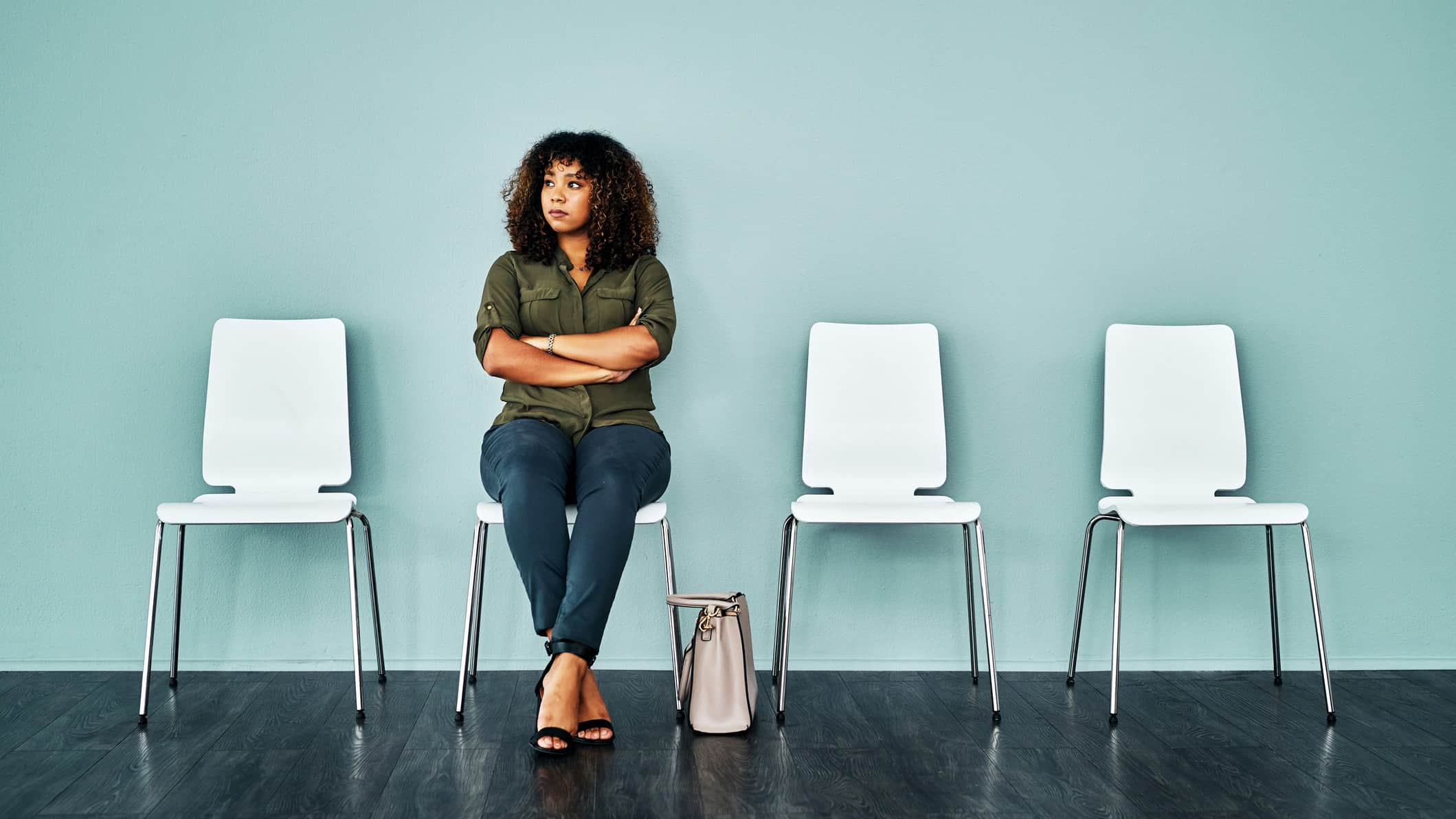 Worried unemployed woman sits on white chair waiting for job interview