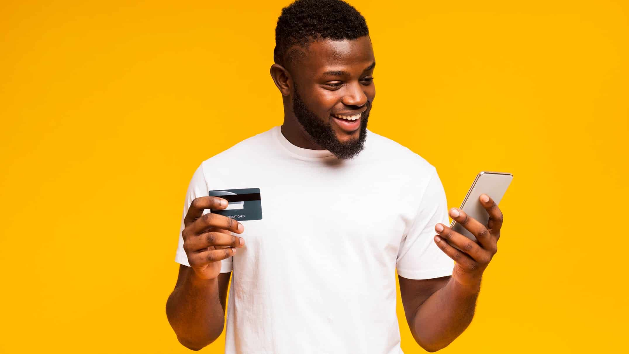 Man in white t-shirt holding Visa card and mobile in front of yellow background