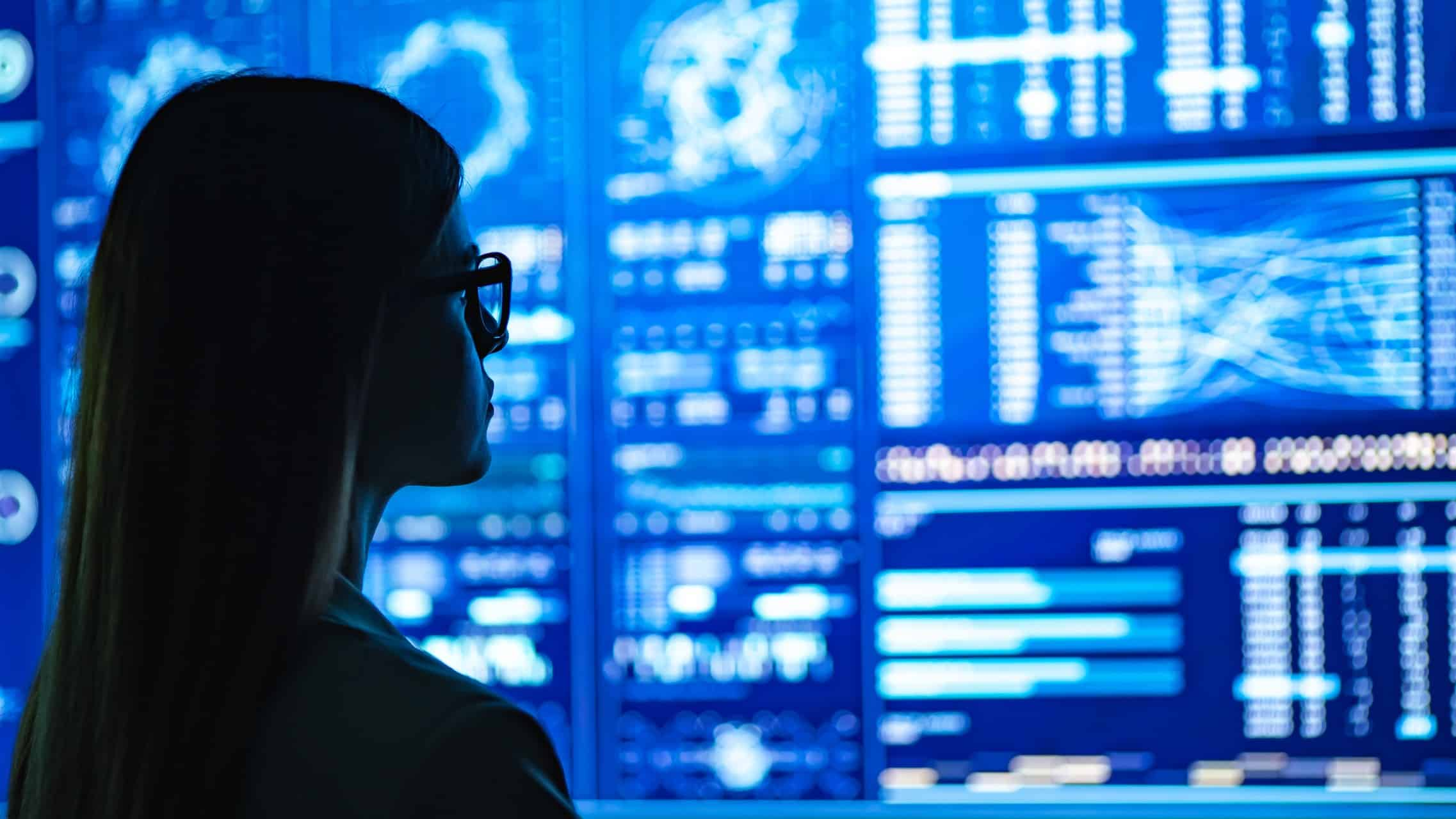 Female investor looking at a wall of share market charts