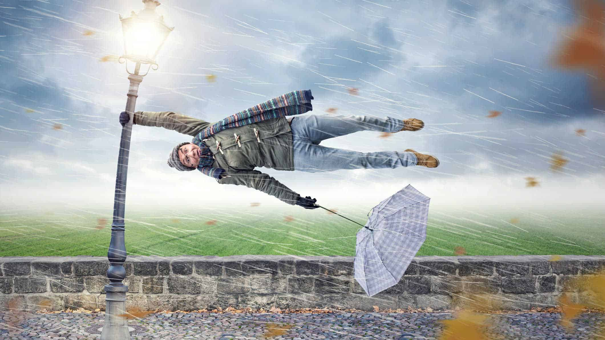 falling asx share price represented by man holding onto pole getting blown in the wind