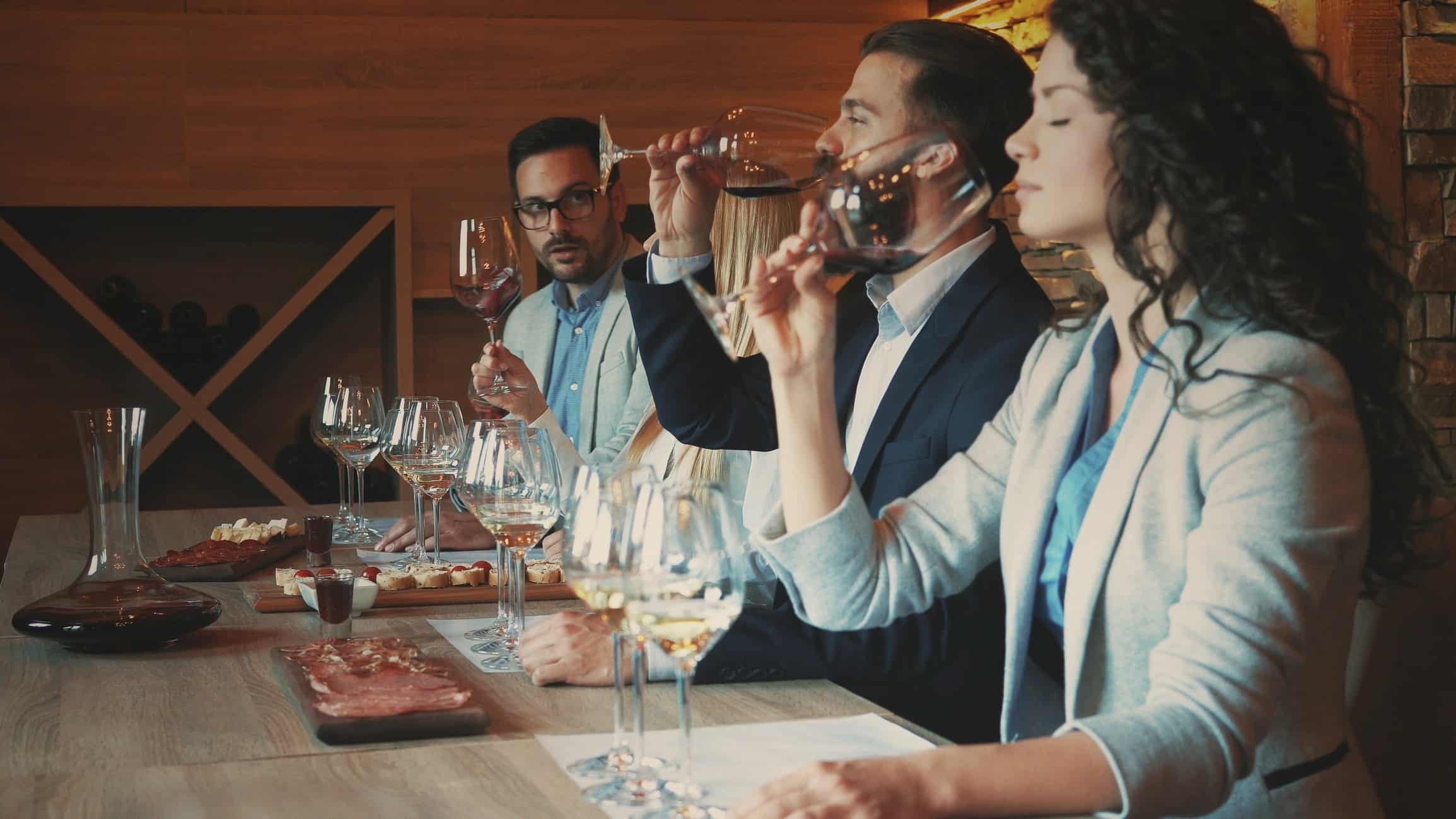 Woman and 2 men conducting a wine tasting