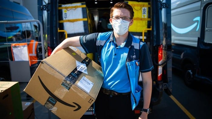amazon.com stock represented by man holding parcel printed with amazon logo