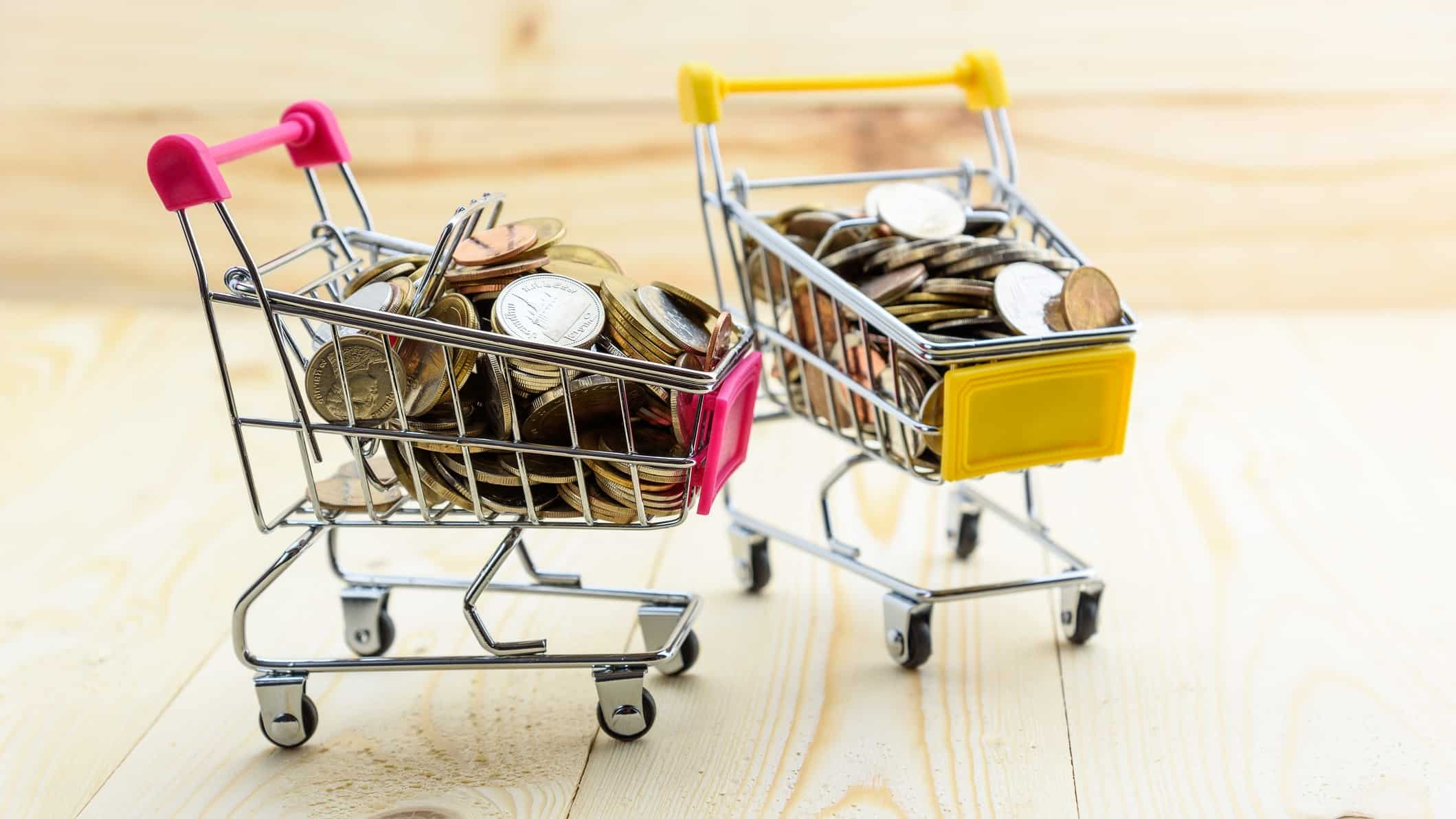 Two miniature shopping trollies filled with coins representing retail ASX growth shares