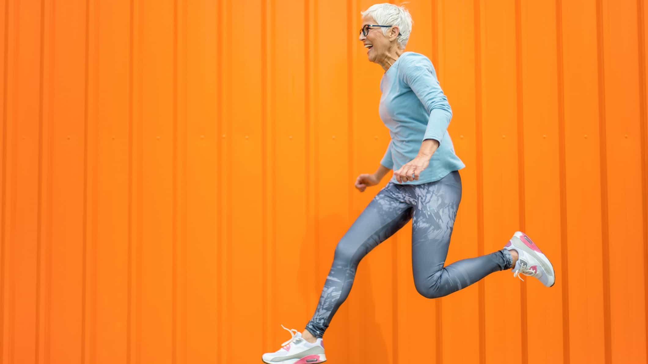 rising asx share price represented by senior lady jumping against orange background