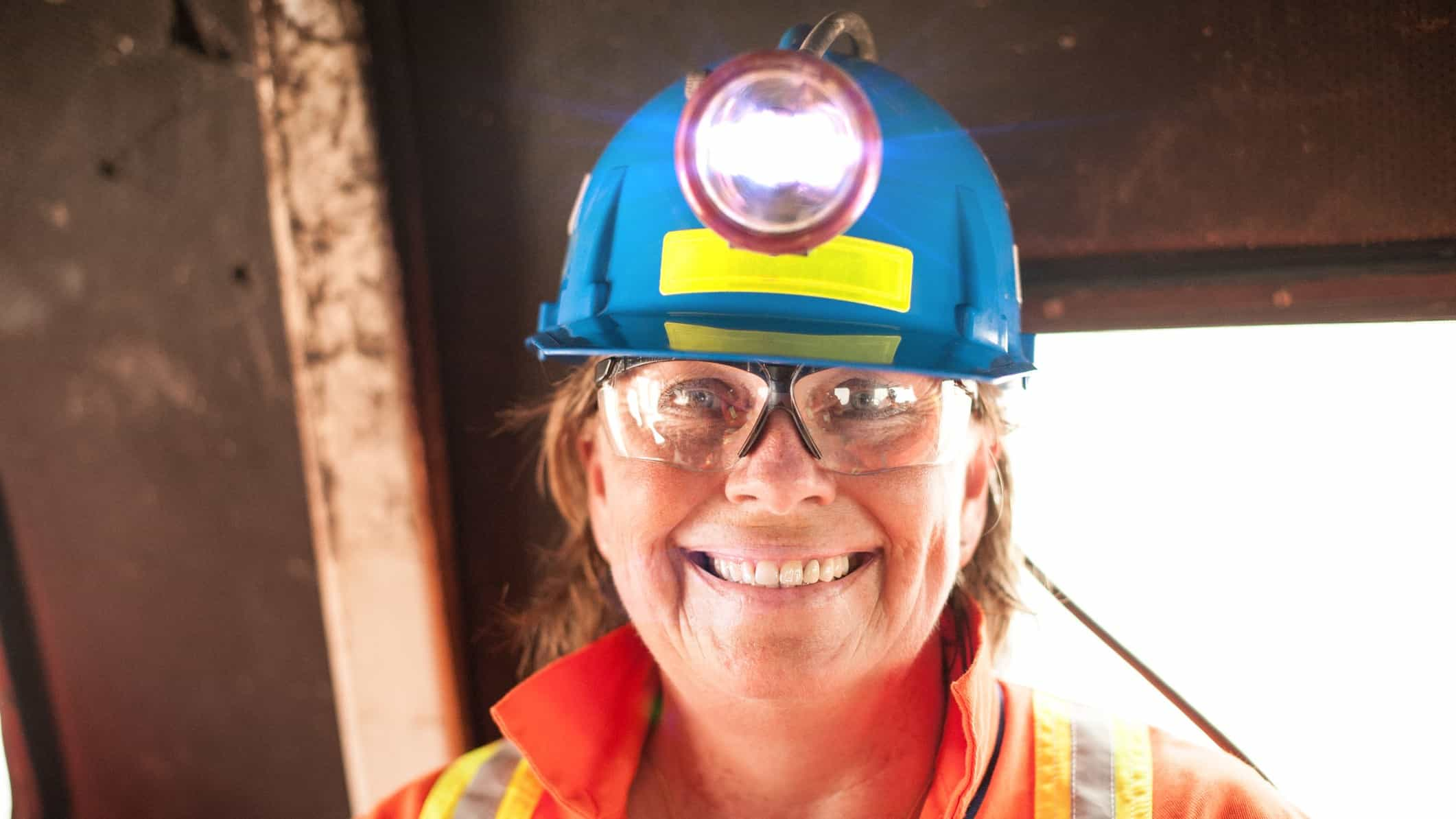 rising mining asx share price represented by happy woman miner in hard hat