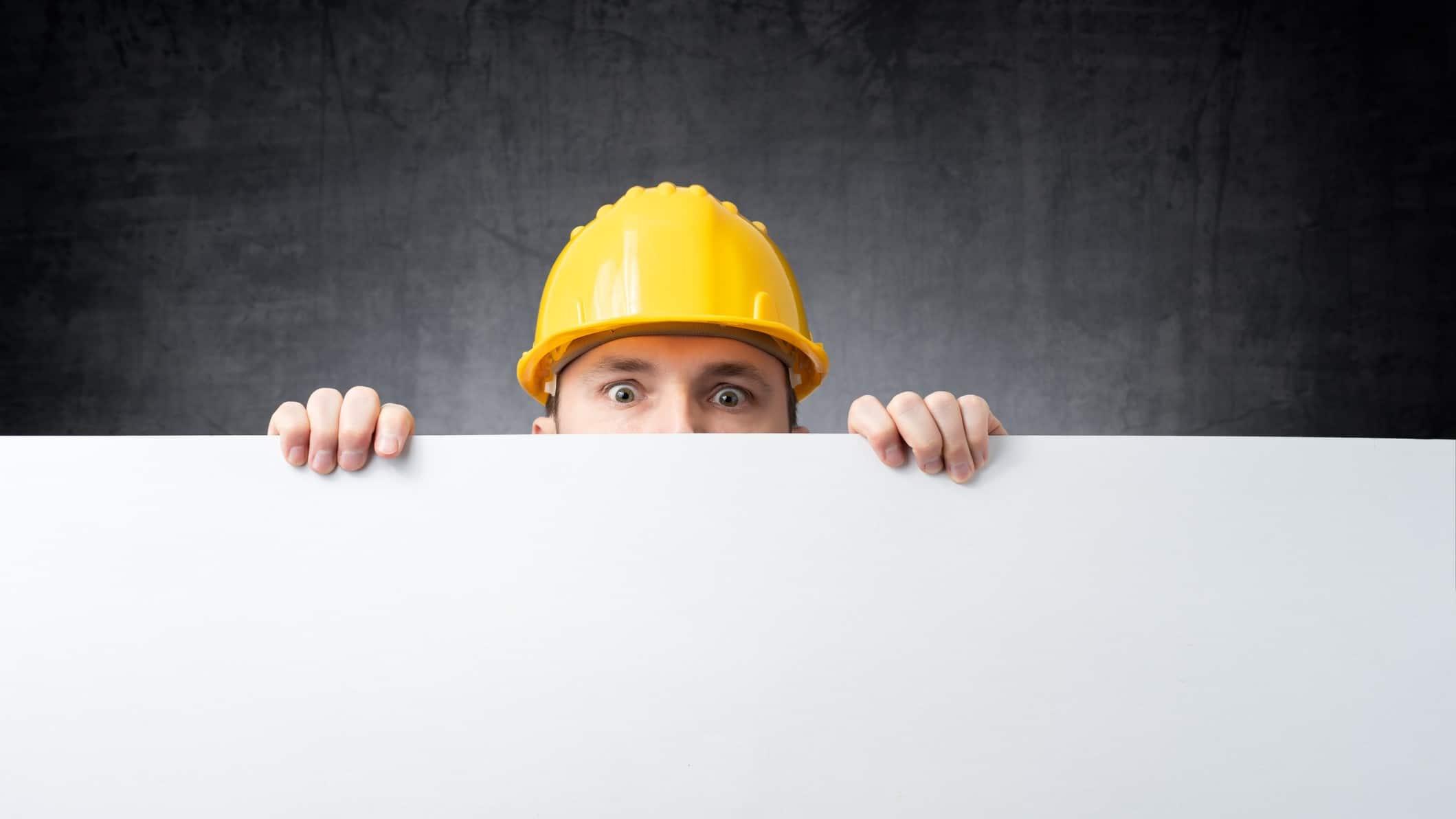 builder peeking over board as if watching asx share price