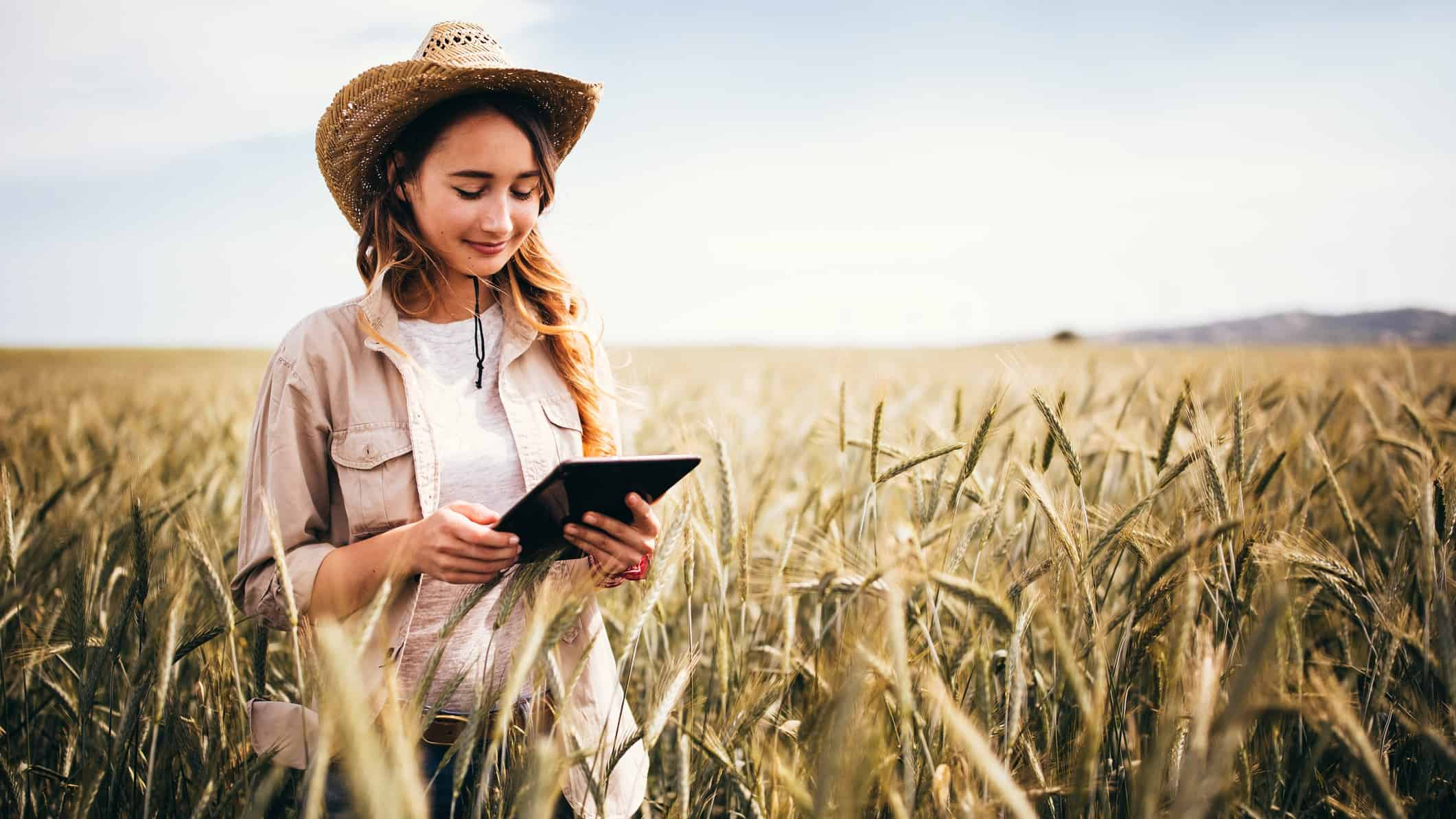 Agricultural ASX share price on watch represented by farmer in field looking at tablet computer