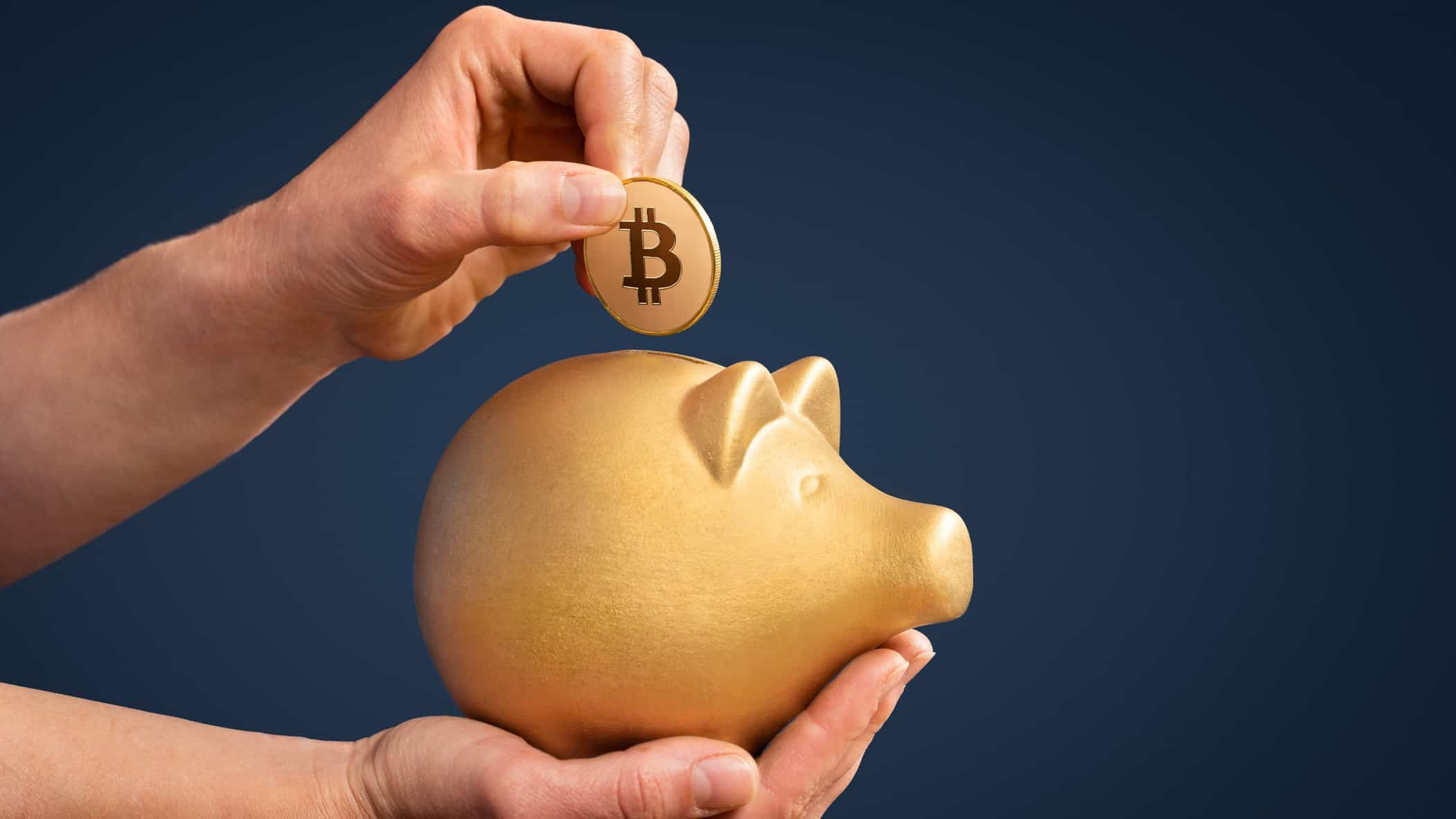 asx share price reacting to bitcoin represented by hand placing bitcoin in gold piggy bank