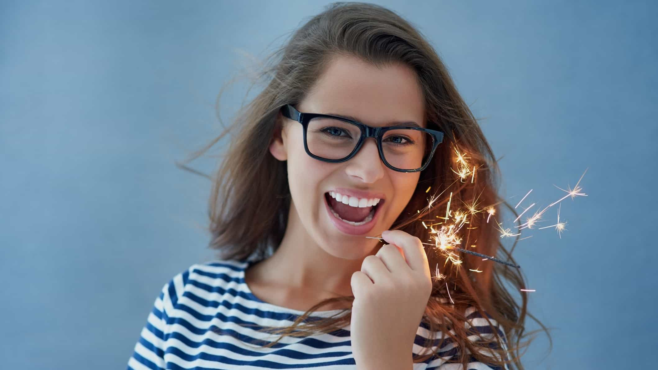 asx share price spark represented by smiling lady holding sparkler