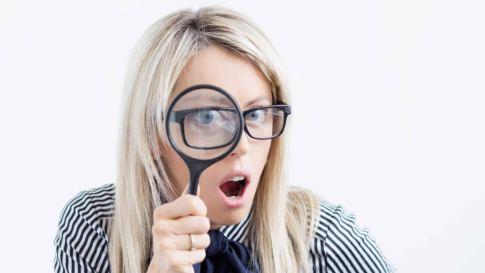 asx share price on watch represented by investor looking through magnifying glass