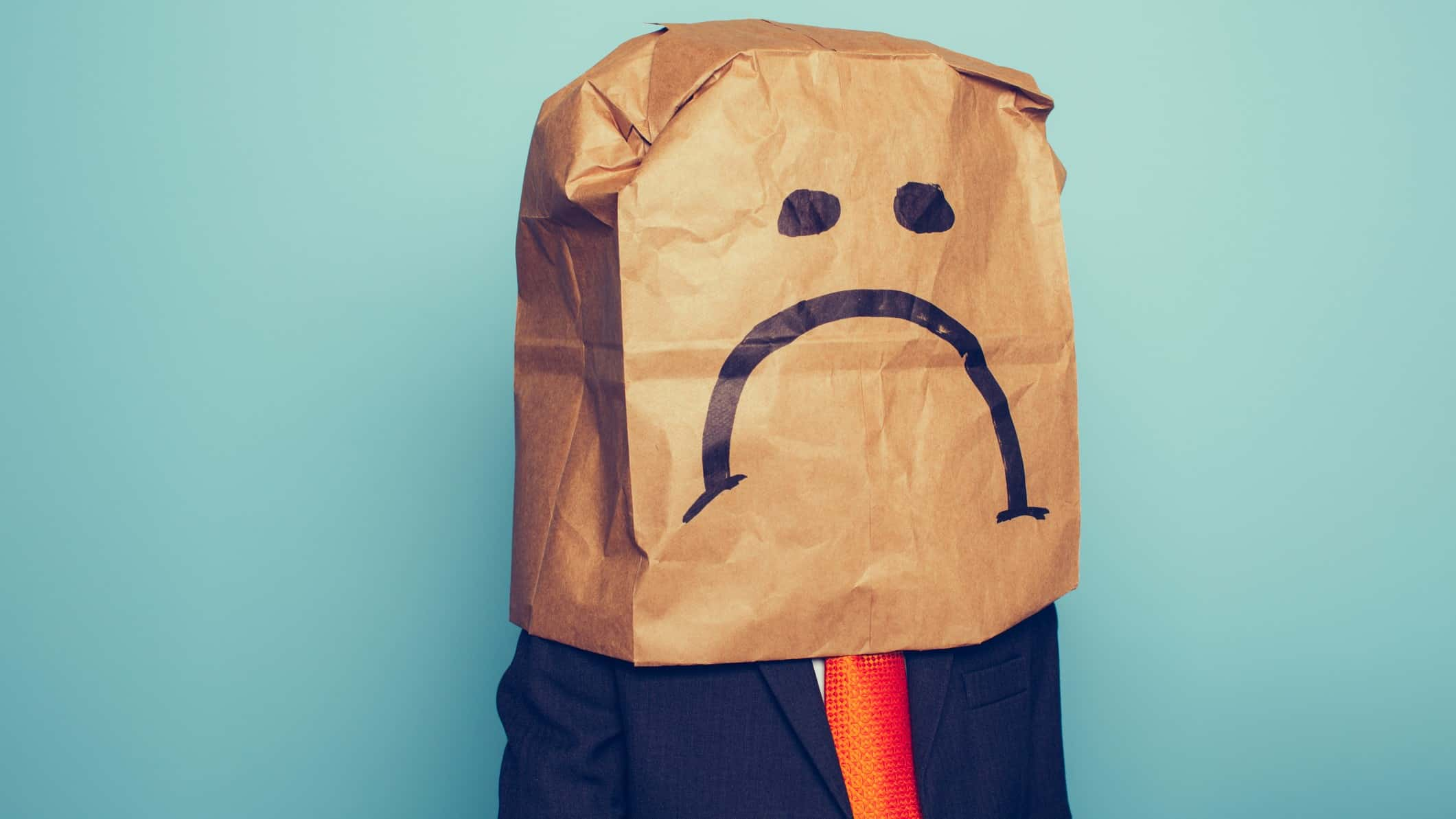 asx share price falling lower represented by investor wearing paper bag on head with sad face