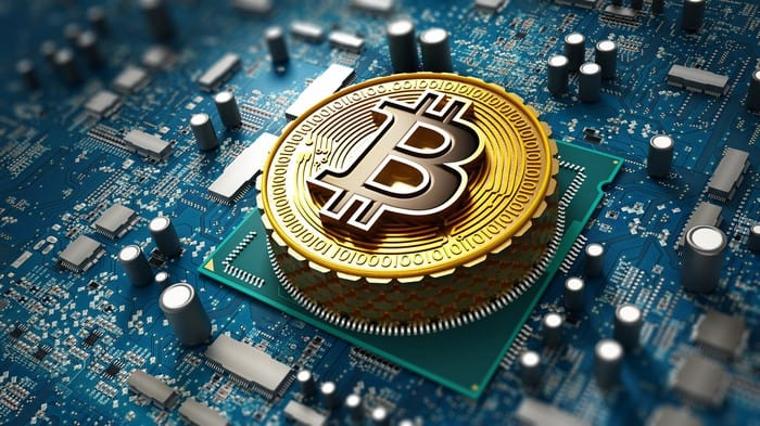 bitcoin represented by gold coin with letter b sitting atop circuit board