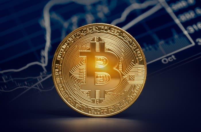 A bitcoin with a chart in the background showing share price movement