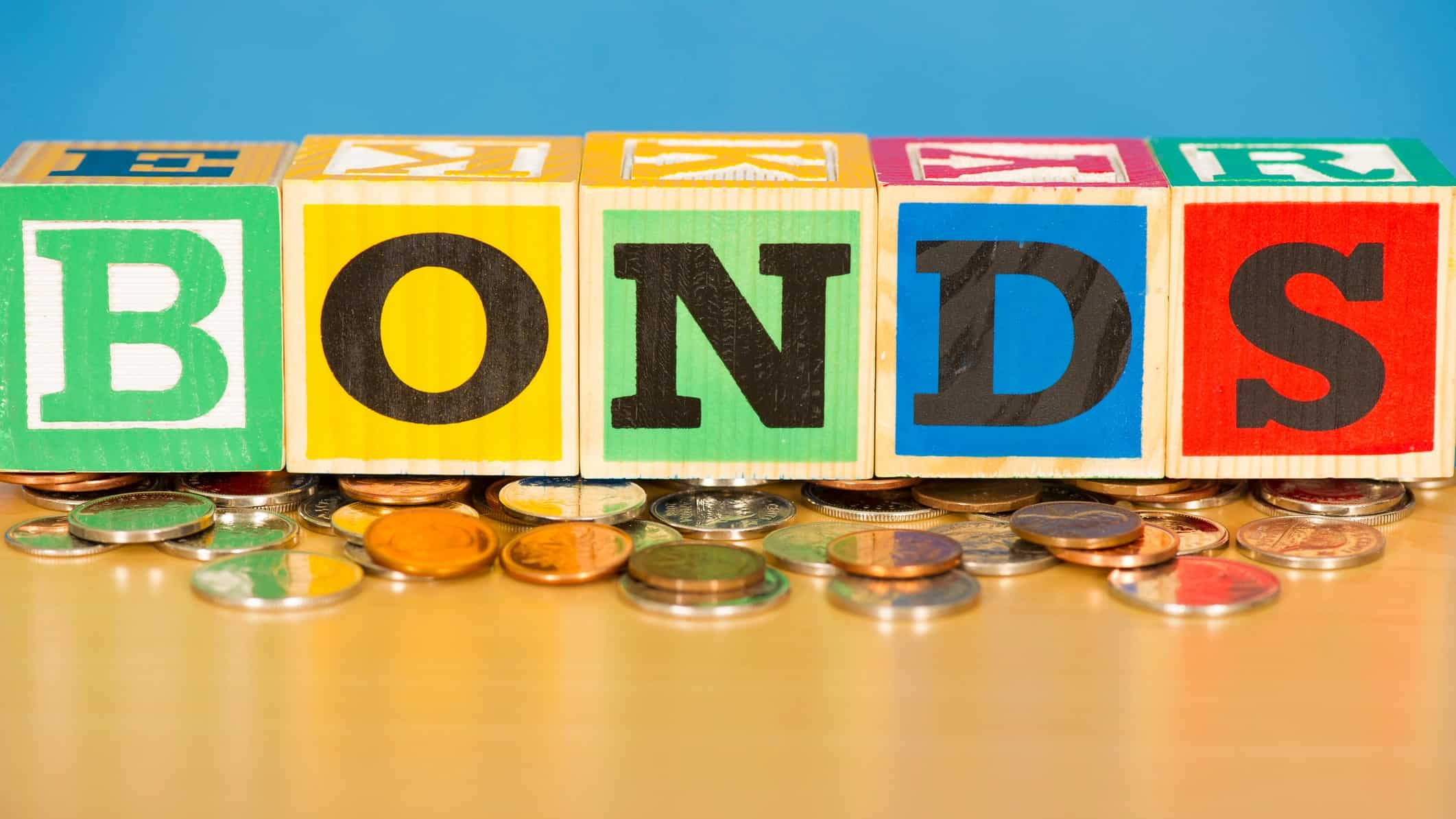 bond yields represented by wooden blocks spelling bonds atop coins
