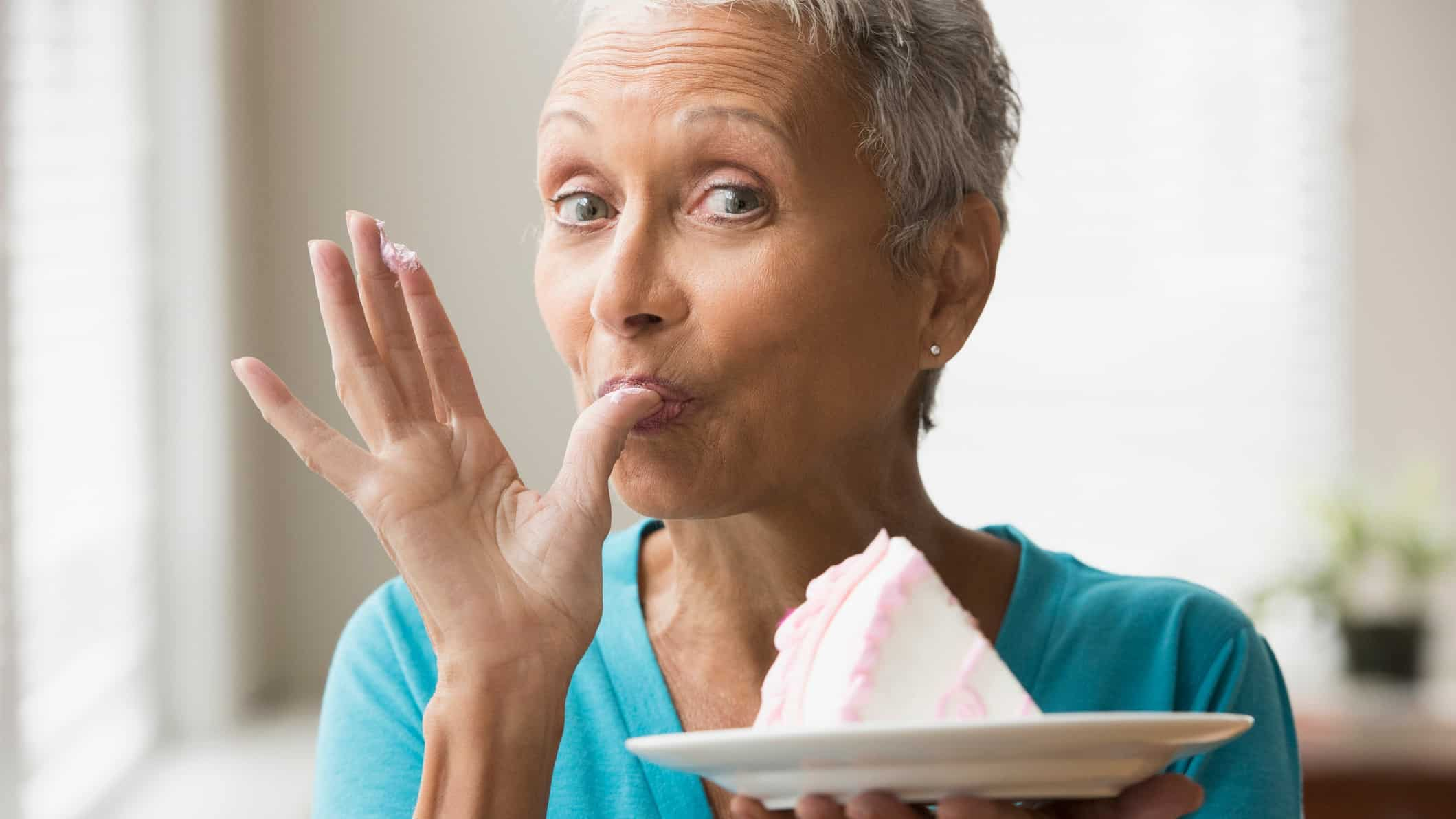 A mature woman hold a plate of cake, licks her thumb, indicating a share price dynamic of 'have your cake and eat it too'
