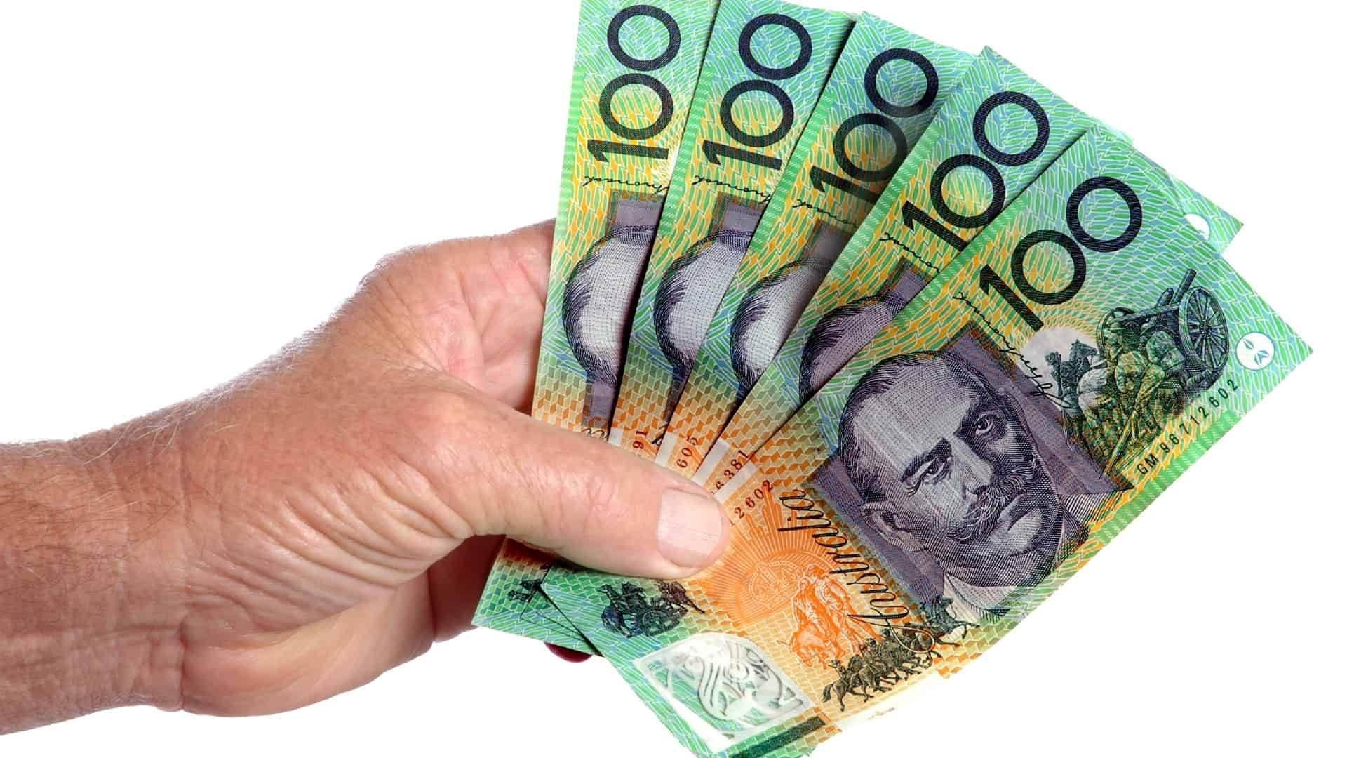 A handful of Australian $100 notes, indicating a cash position