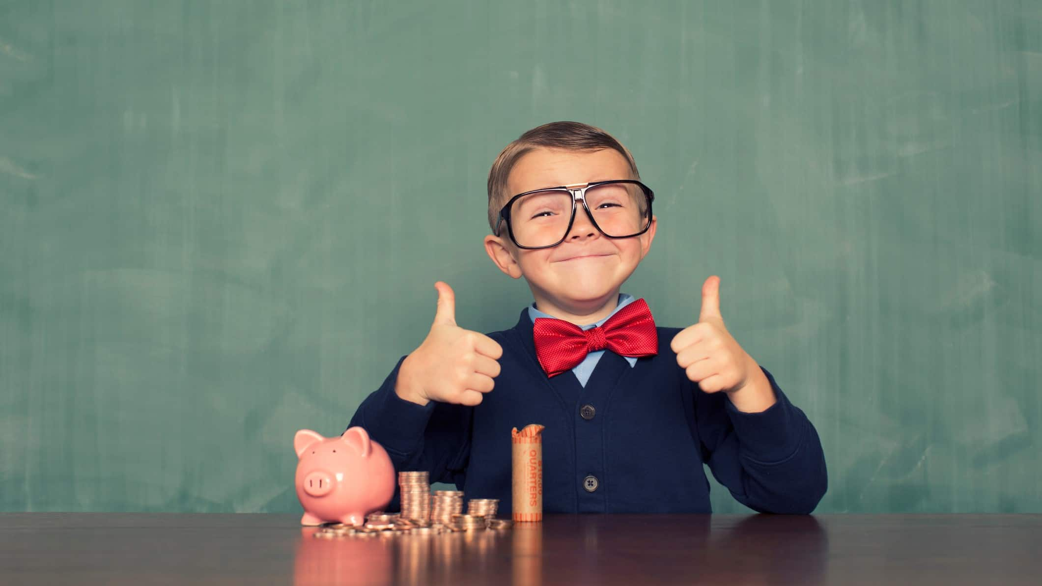 cheap shares represented by boy in business suit giving thumbs up with piggy banks and coin piles