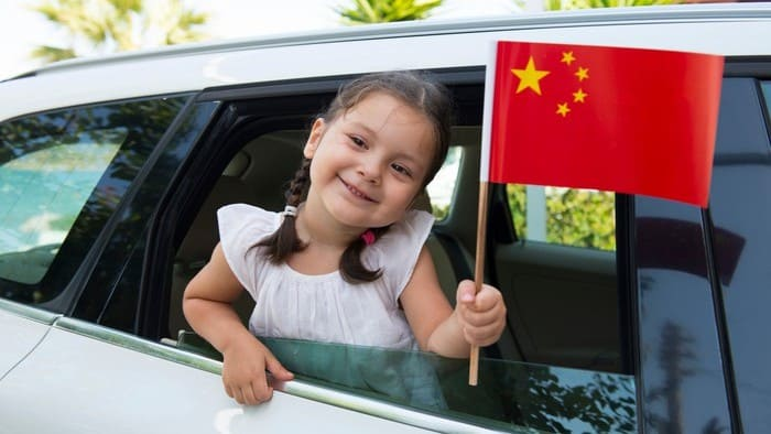 girl holding out a Chinese flag through a window