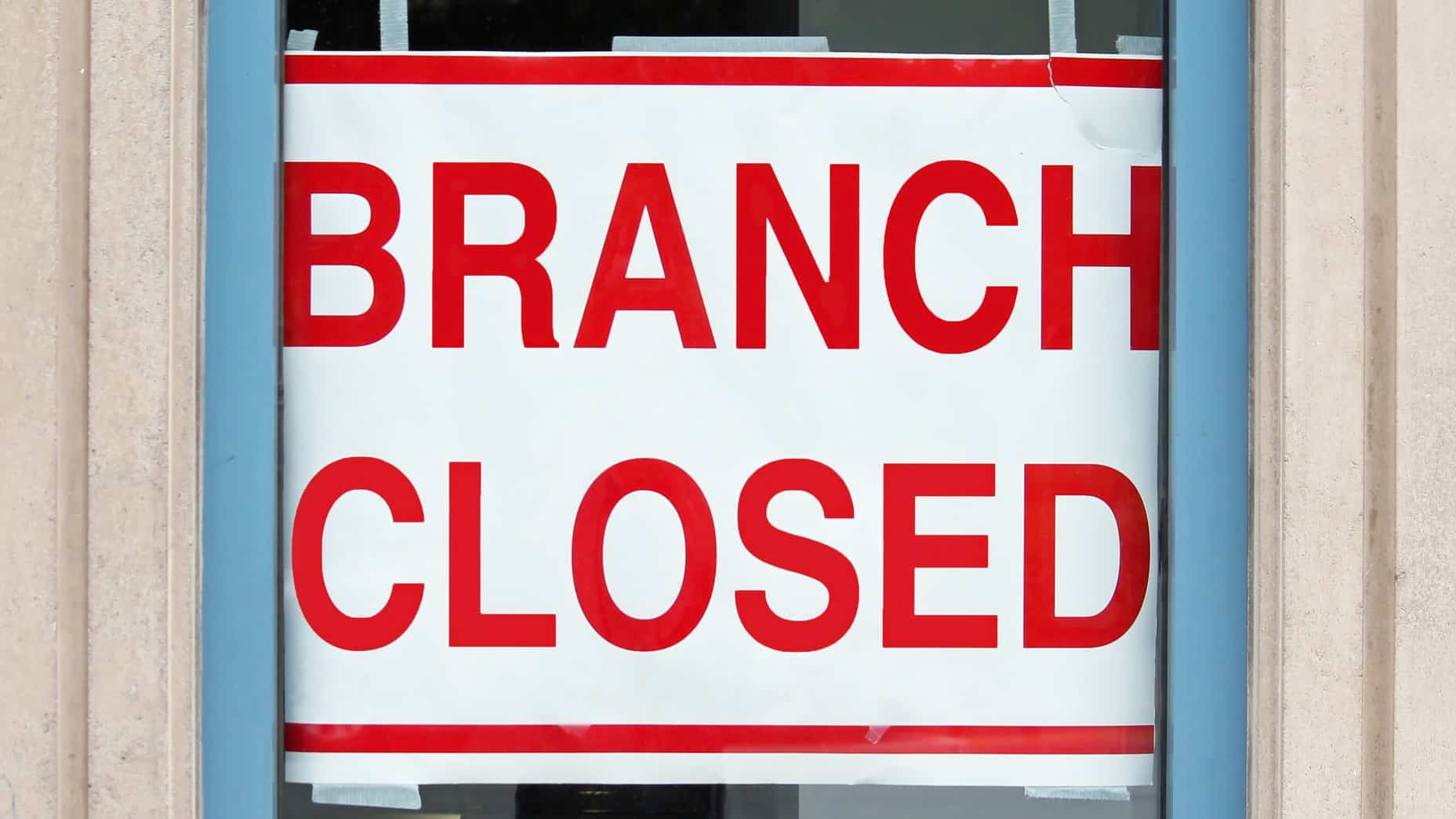 A sign stuck to a bank window says 'branch closed', indicating share price pressure on ASX bank shares