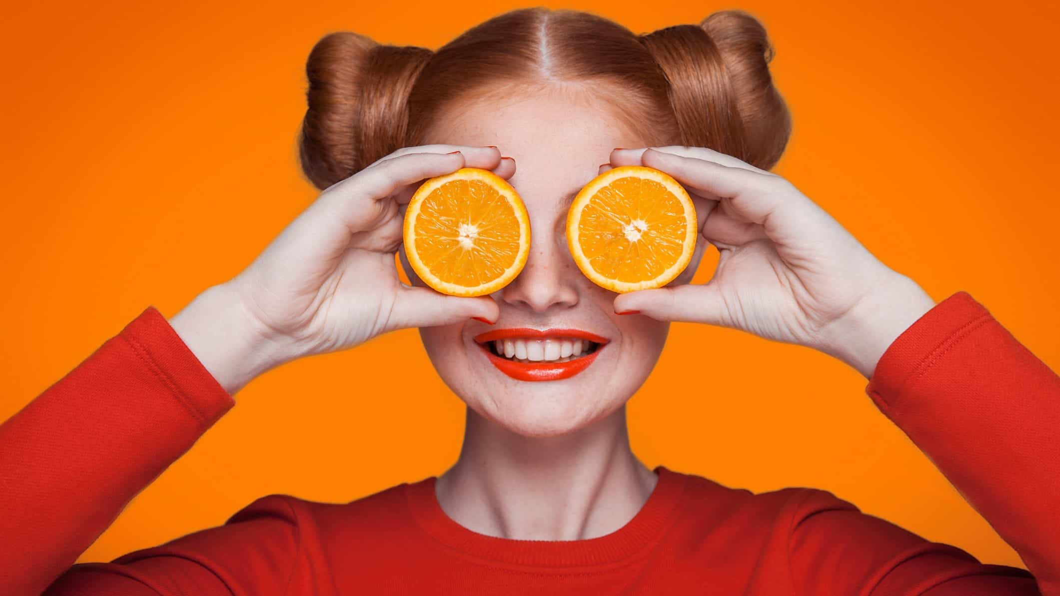 A smiling woman holds slices of orange to her eyes, indicating share price rises for ASX commodity shares