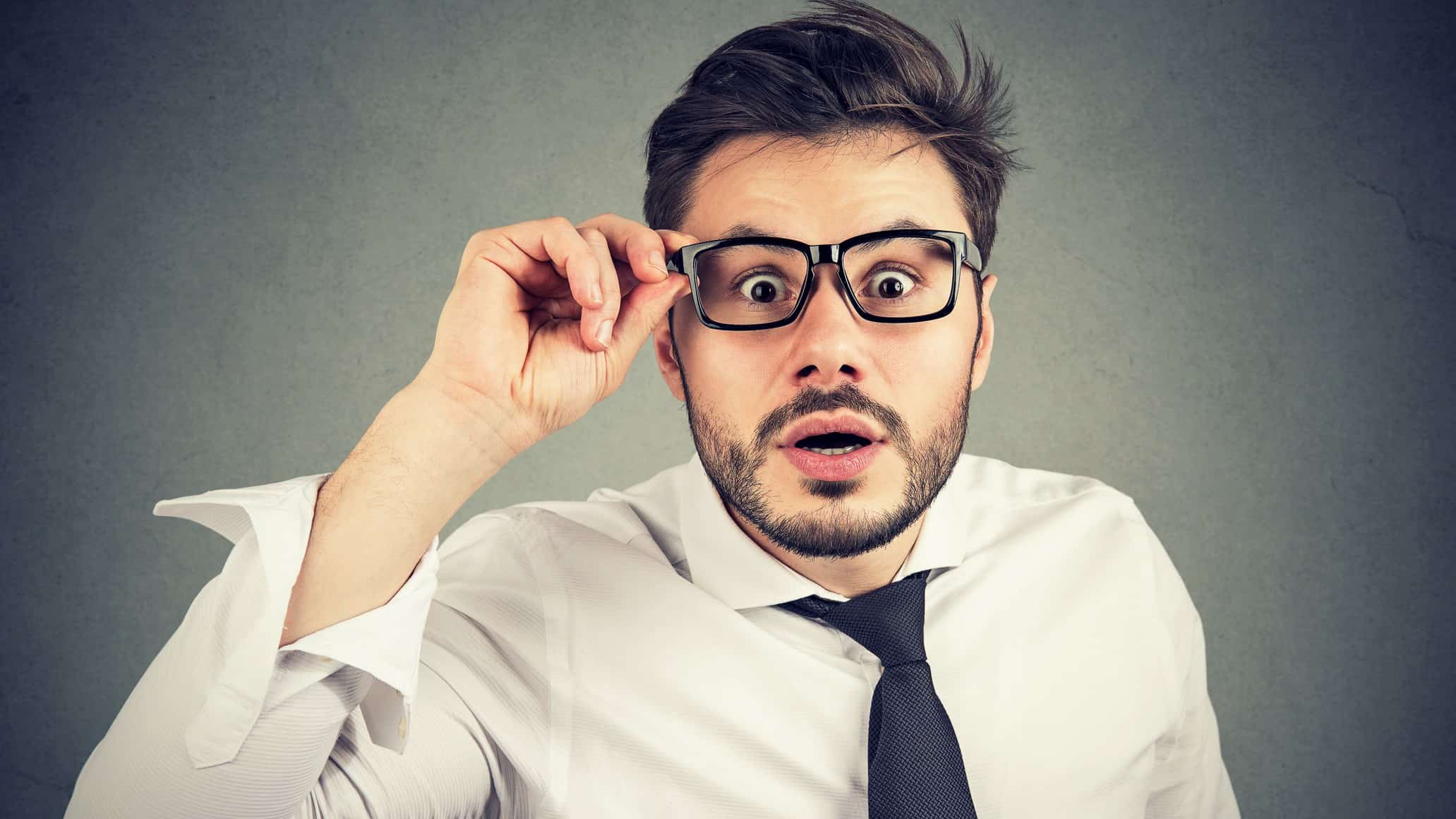A businessman holds his glasses in concern, indicating uncertainly in the ASX share price