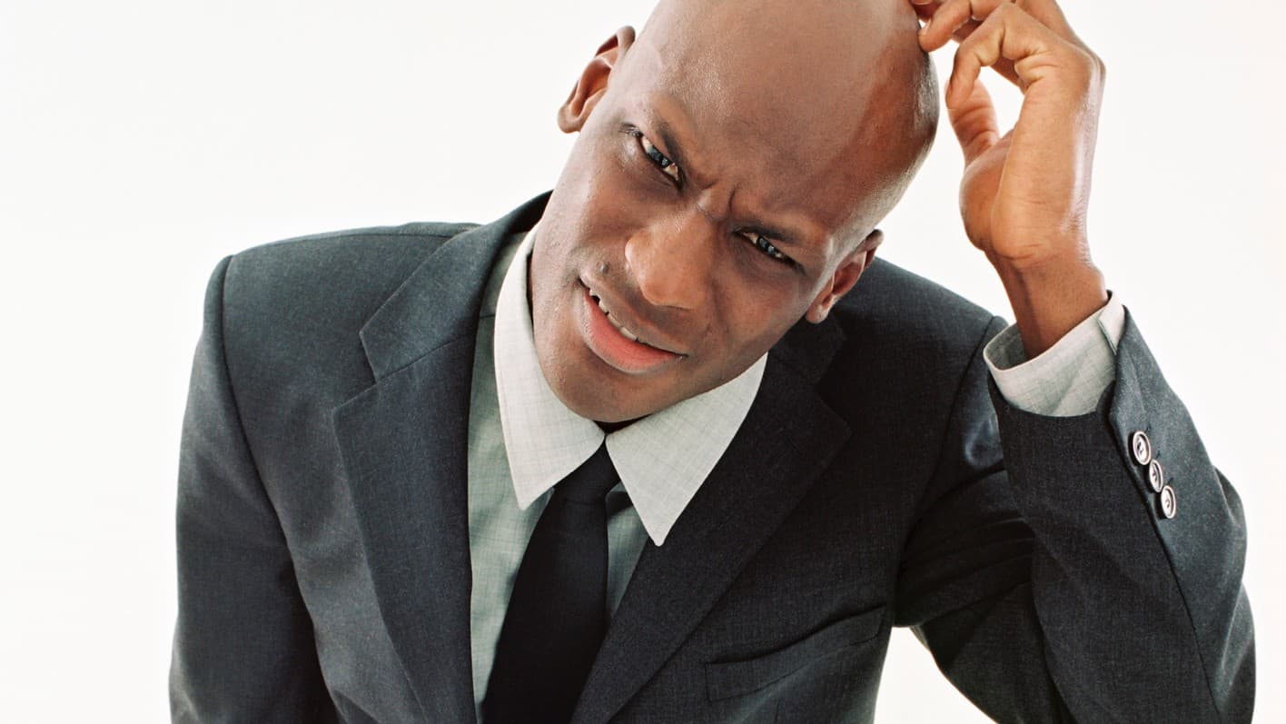 A man scratches his head in confusion., indicating mixed share price movement on the ASX