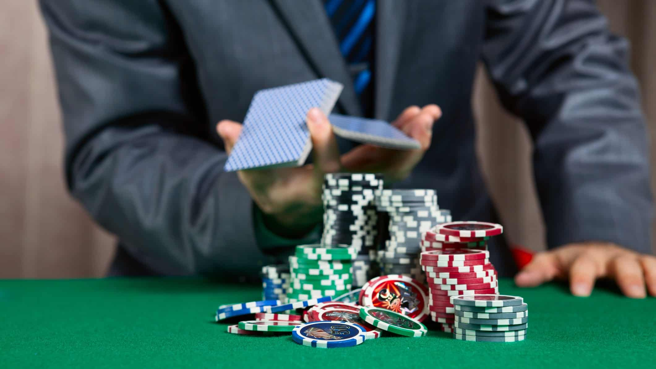 man playing cards with casino chips representing crown share price