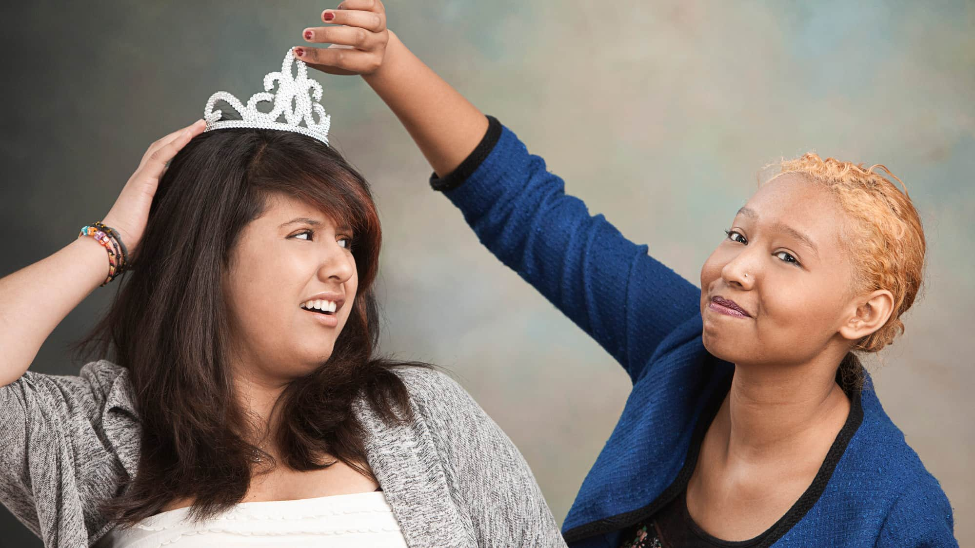 A young woman holds onto her crown as another moves to take it, indicating rival ASX shares