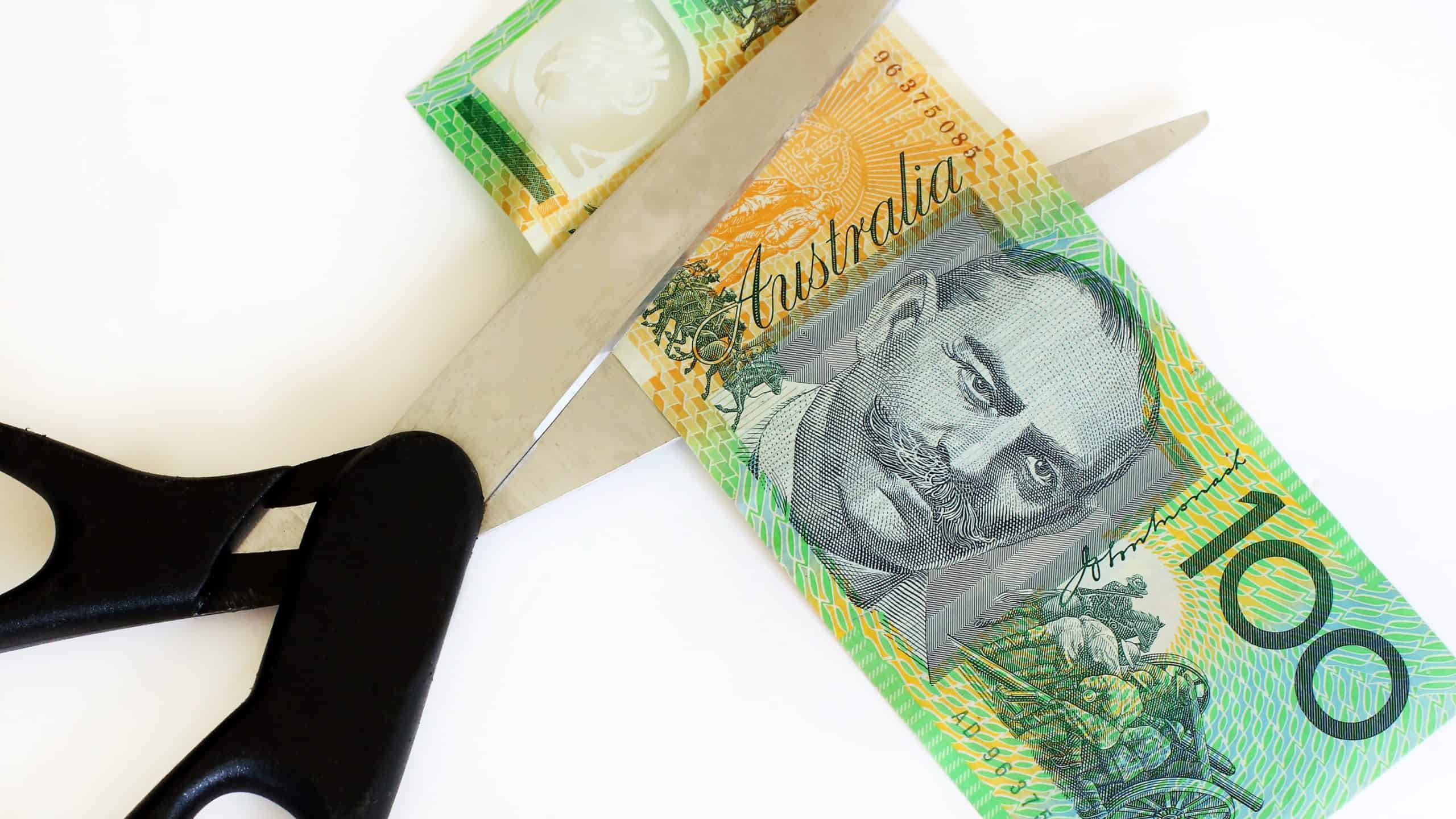 pair of scissors cutting one hundred dollar note representing cut dividend