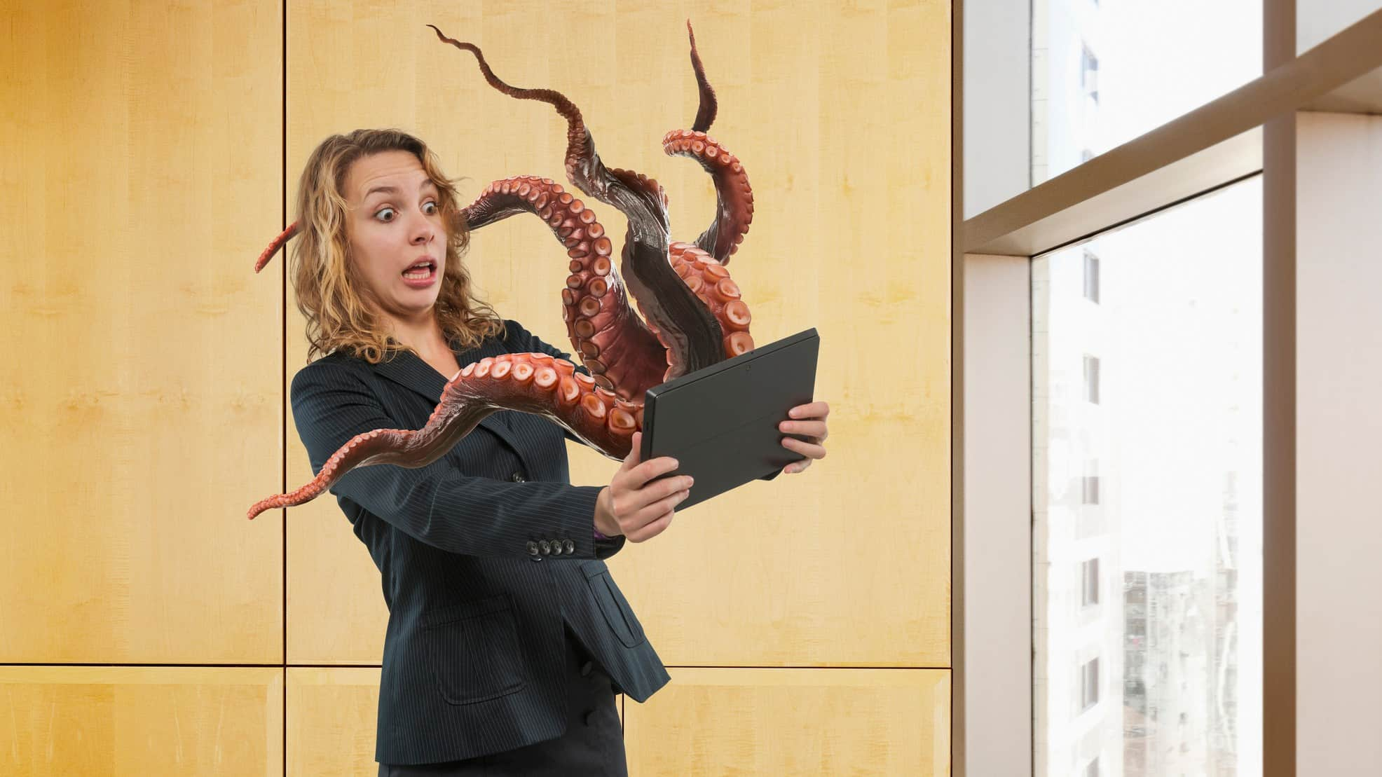 cybersecurity shares represented by octopus reaching out of computer screen towards woman