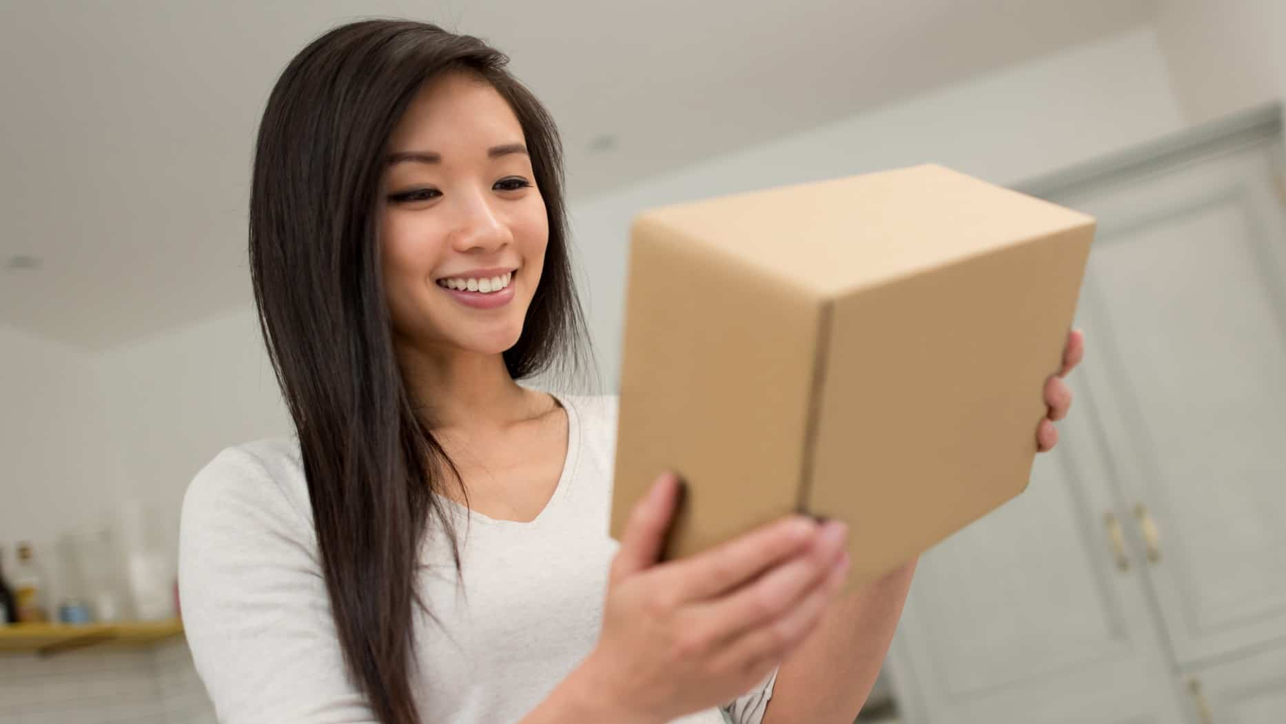 daigou asx 200 shares represented by woman receiving brown package in the mail