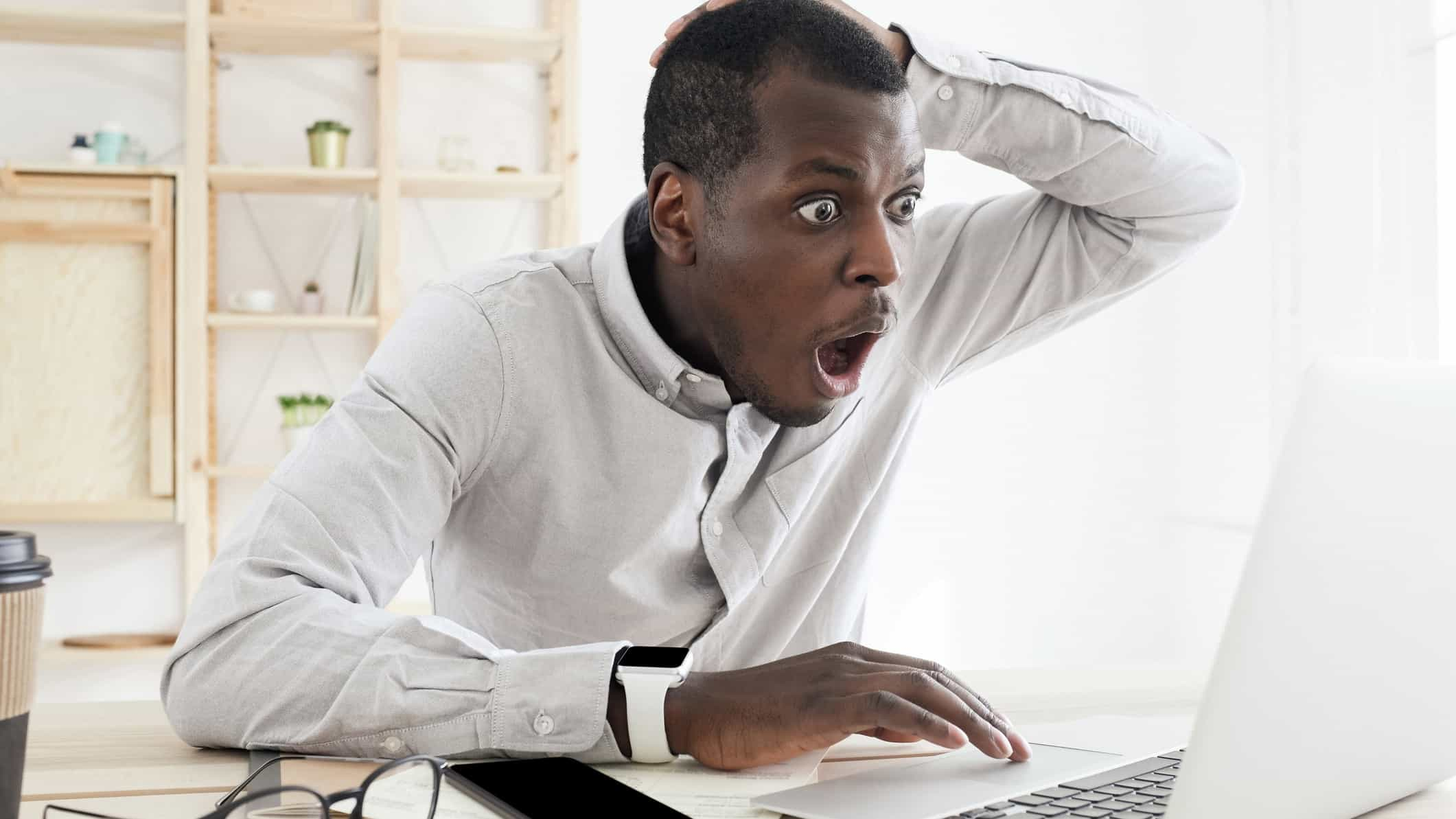 An ASX investor looks devastated as he watches his computer screen, indicating bad news