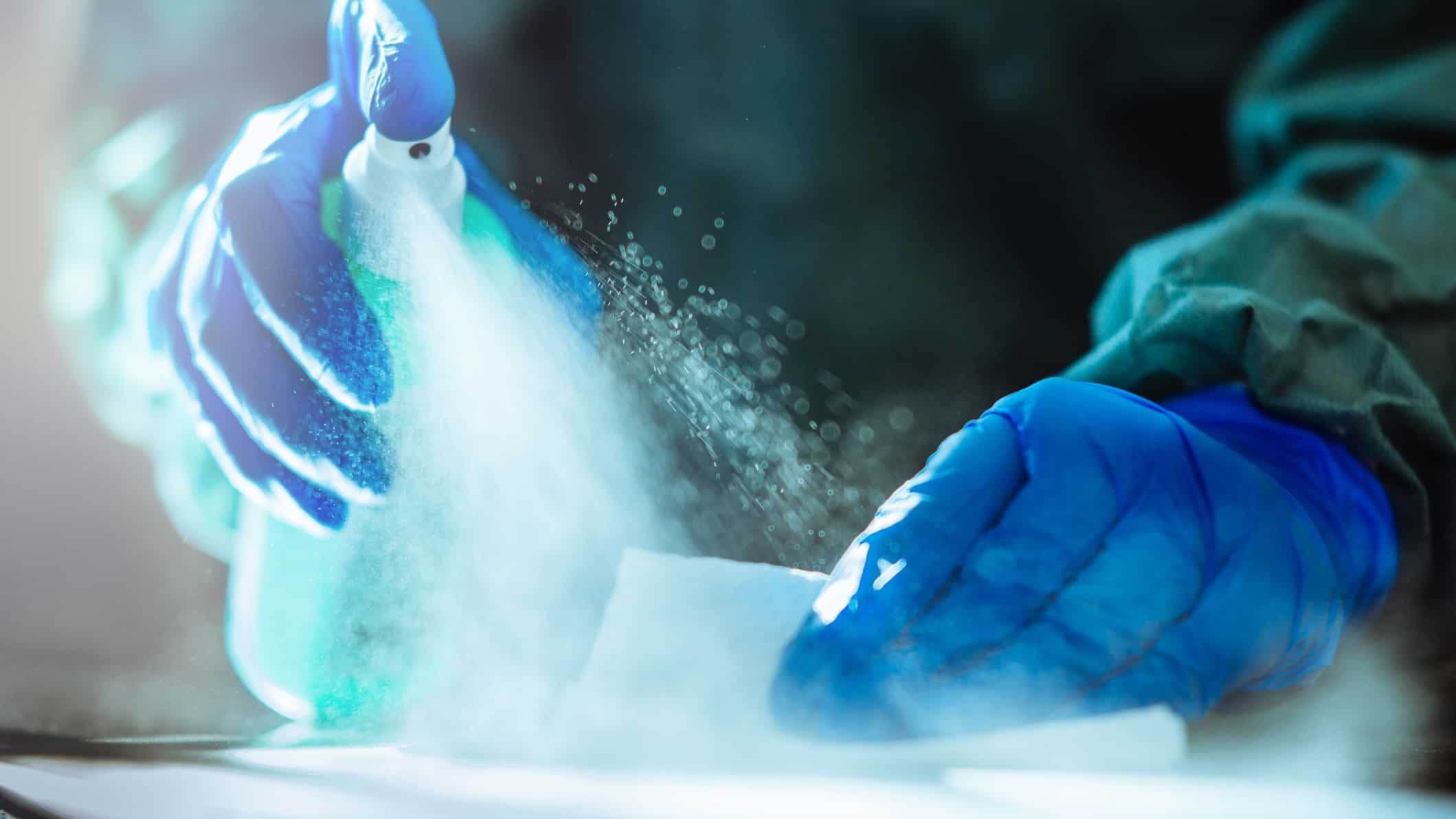 Two hands with gloves spray disinfectant onto a surface, indicating share price movements for ASX biotech companies