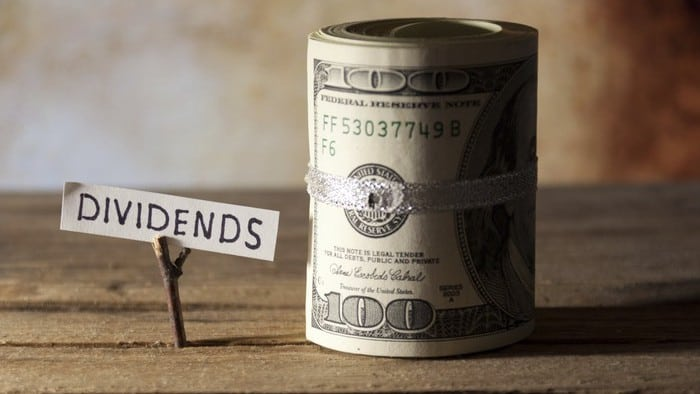 Dividend stocks represented by paper sign saying dividends next to roll of cash