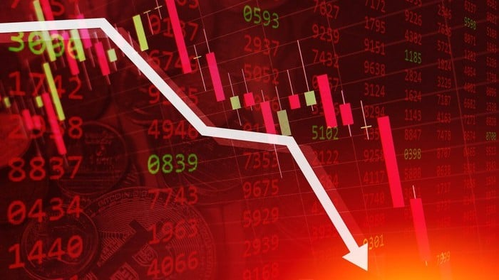 A stockmarket chart on a red background with an arrow going down, indicating falling share price