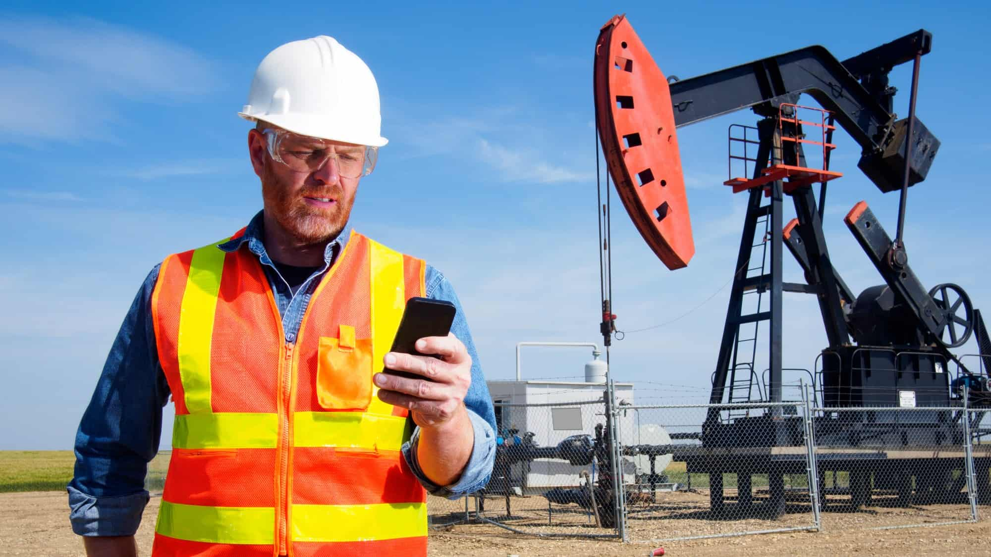 A worried miner looks at his phone in front of a massive drilling, indicating a share price drop for ASX mining companies
