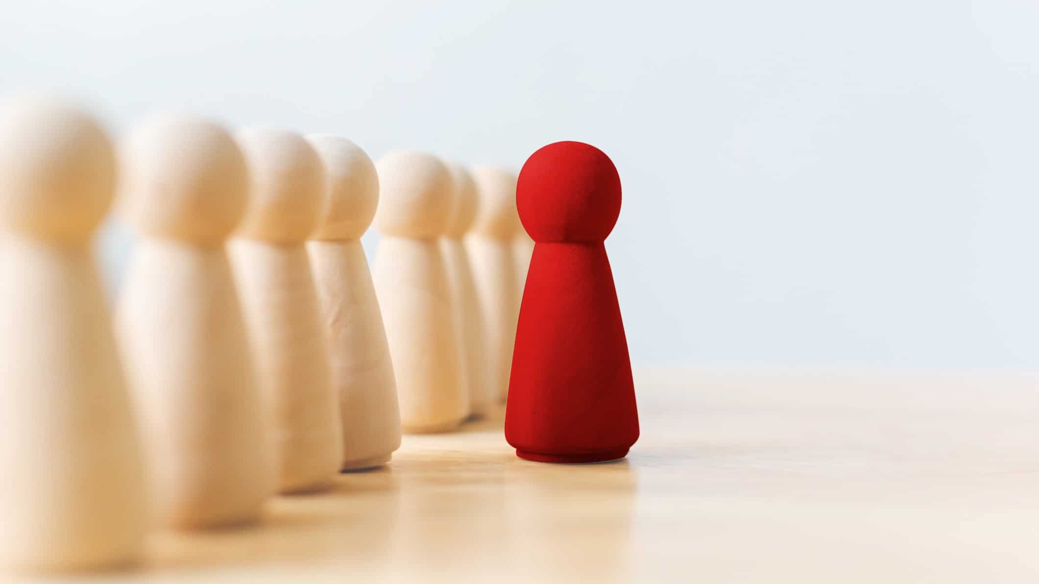 small red wooden peg doll standing ahead of group of neutral coloured peg dolls