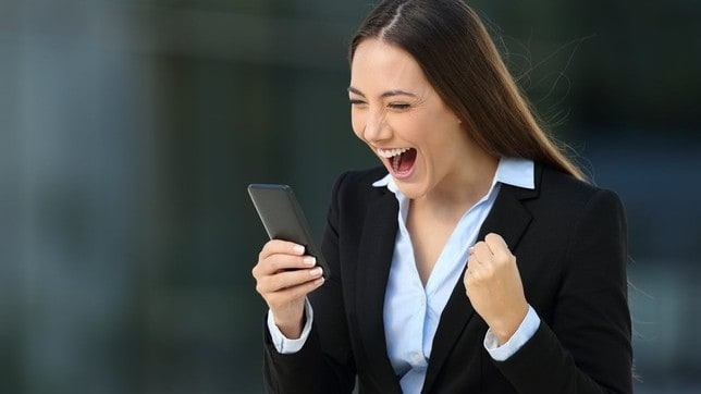 A happy woman looks at her mobile phone and fist pumps, indicating a share price rise