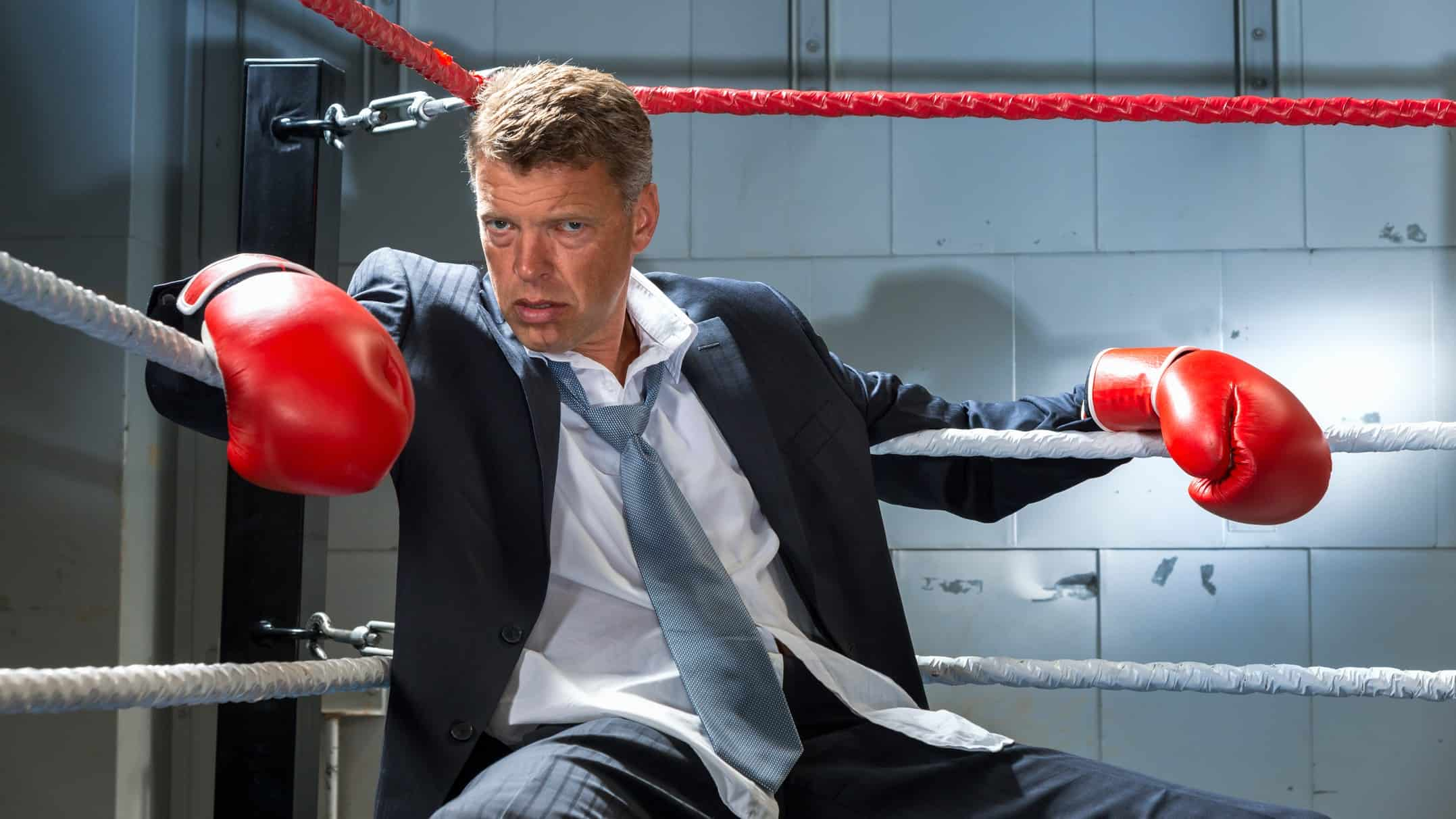 A businessman in a suit and wearing boxing gloves, slump in the corner of a ring, indicating a corporate fight between ASX companies