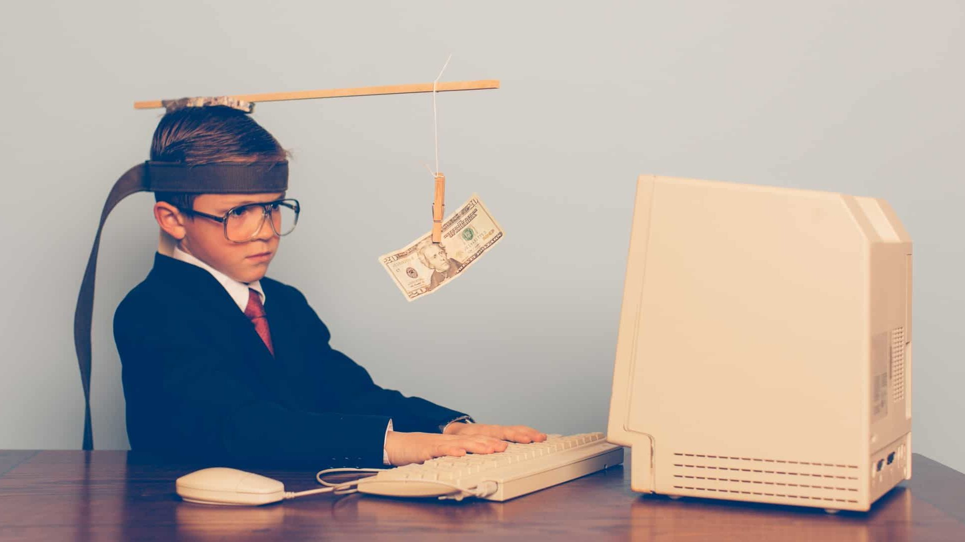 financial plans represented by boy sitting at old computer with dollar note hanging in front of his head