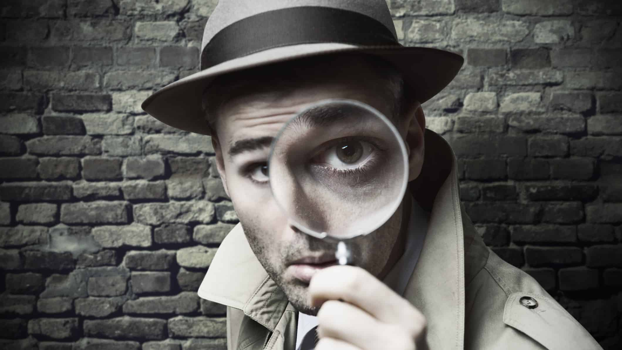 man in old fashioned suit and hat looking through magnifying glass