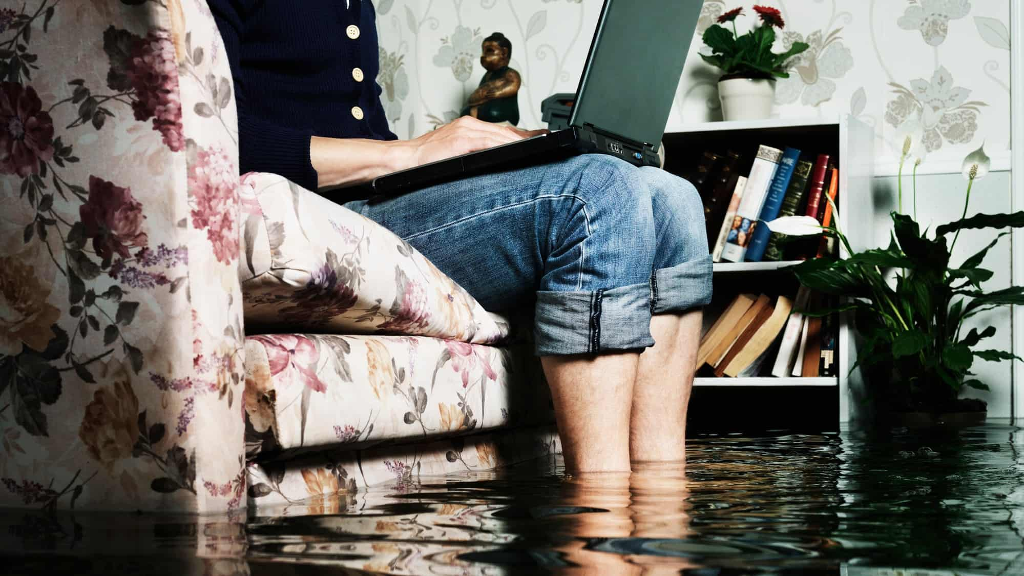 A person sits on a couch with a laptop while flood waters lapping around his legs, indicating a push on insurance companies