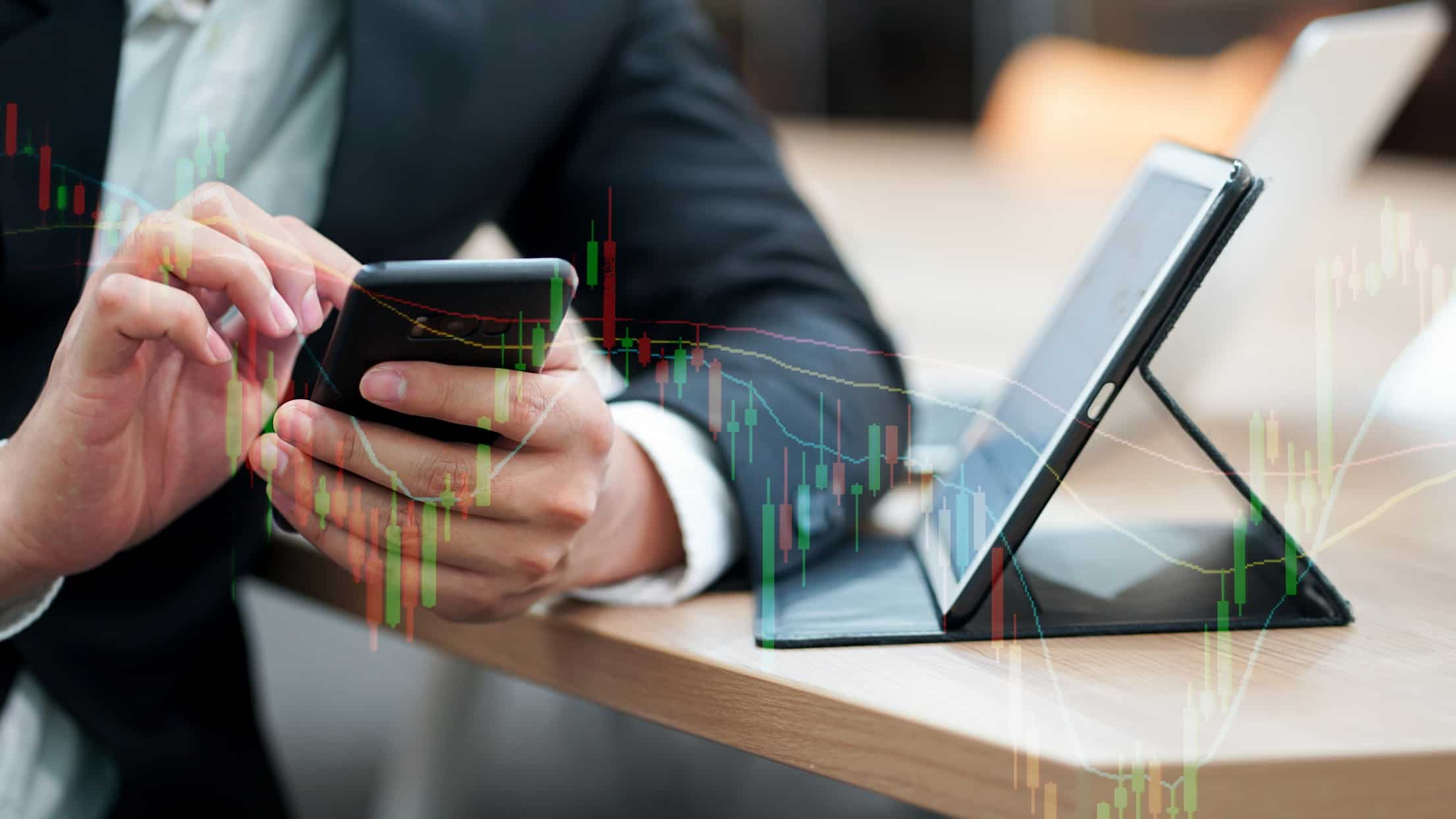 A share market investment manager monitors share price movements on his mobile phone and laptop