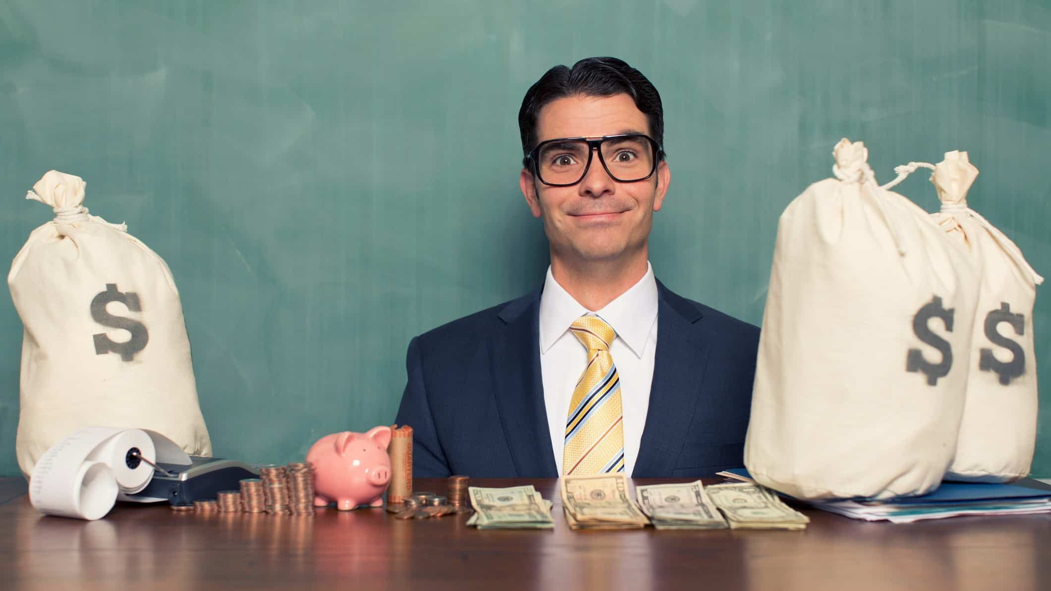A smiling businessman sits at a desk with bags of mony, indicating a share price rise after funding has been approved