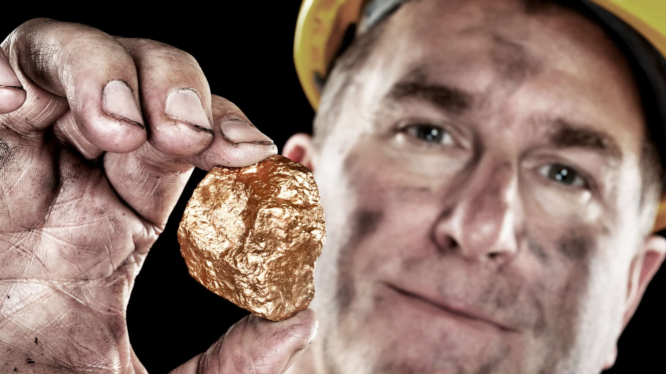 miner holding gold nugget