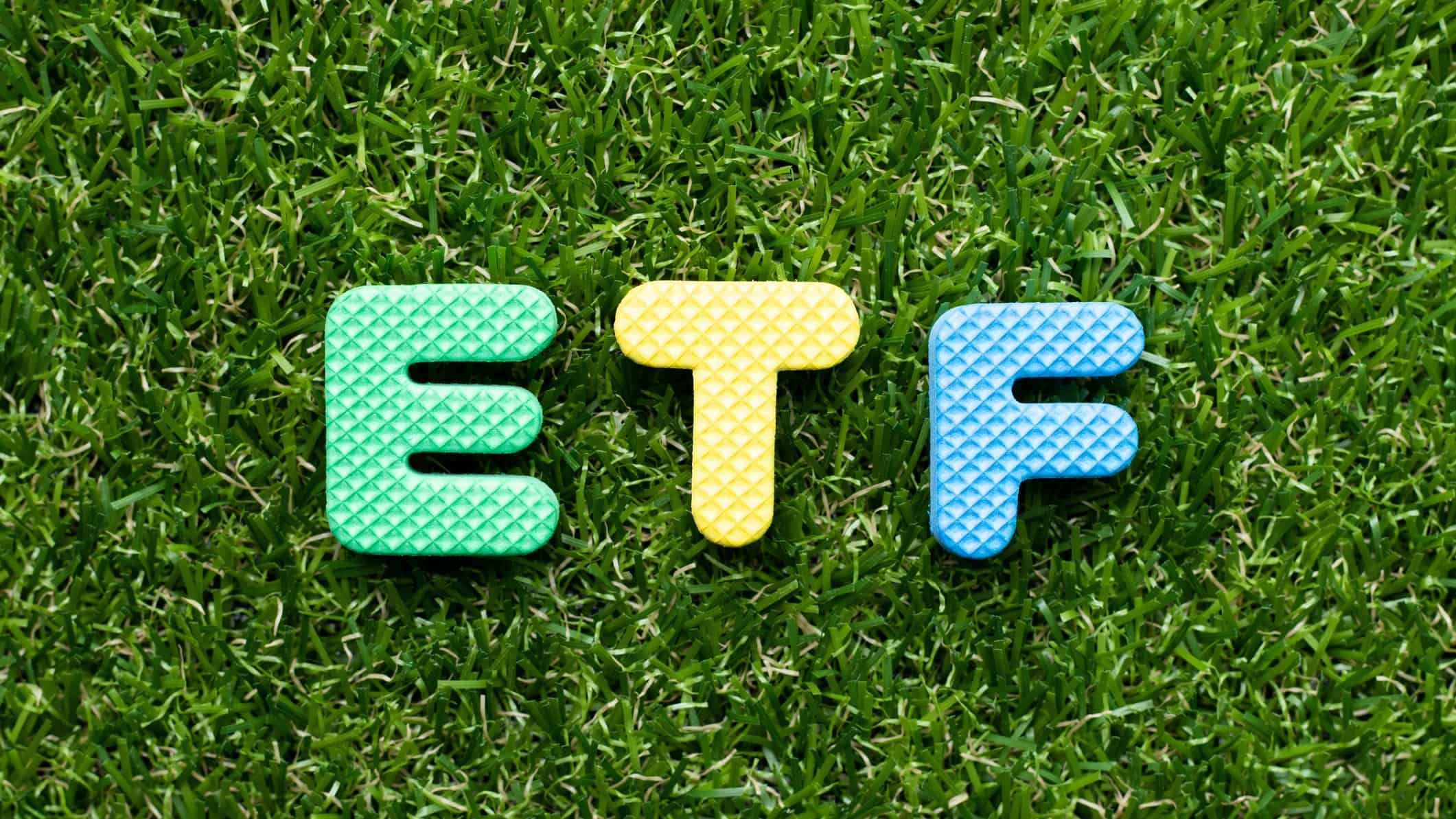 green etf represented by letters E,T and F sitting on green grass