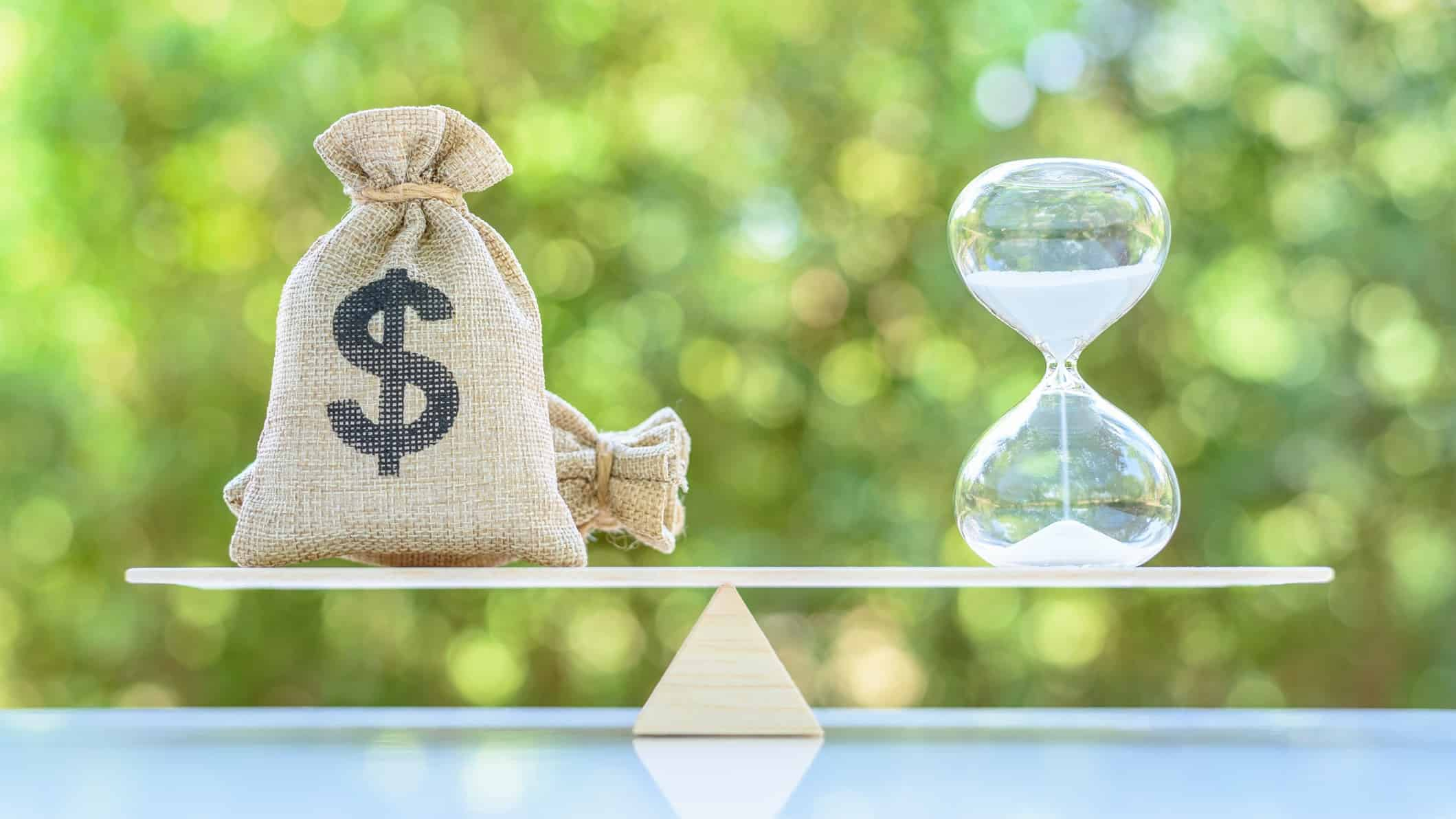 A set of scales with a bag of money balanced against a timer, indicating growth versus value shares