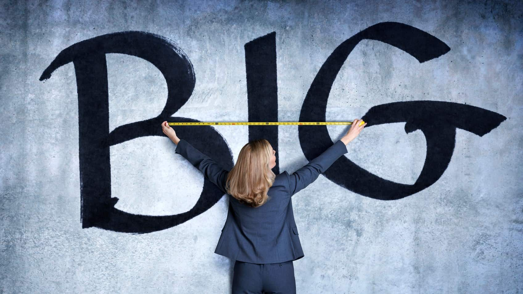 A woman holds a tape measure against a wall painted with the word BIG, indicating a surge in gowth shares