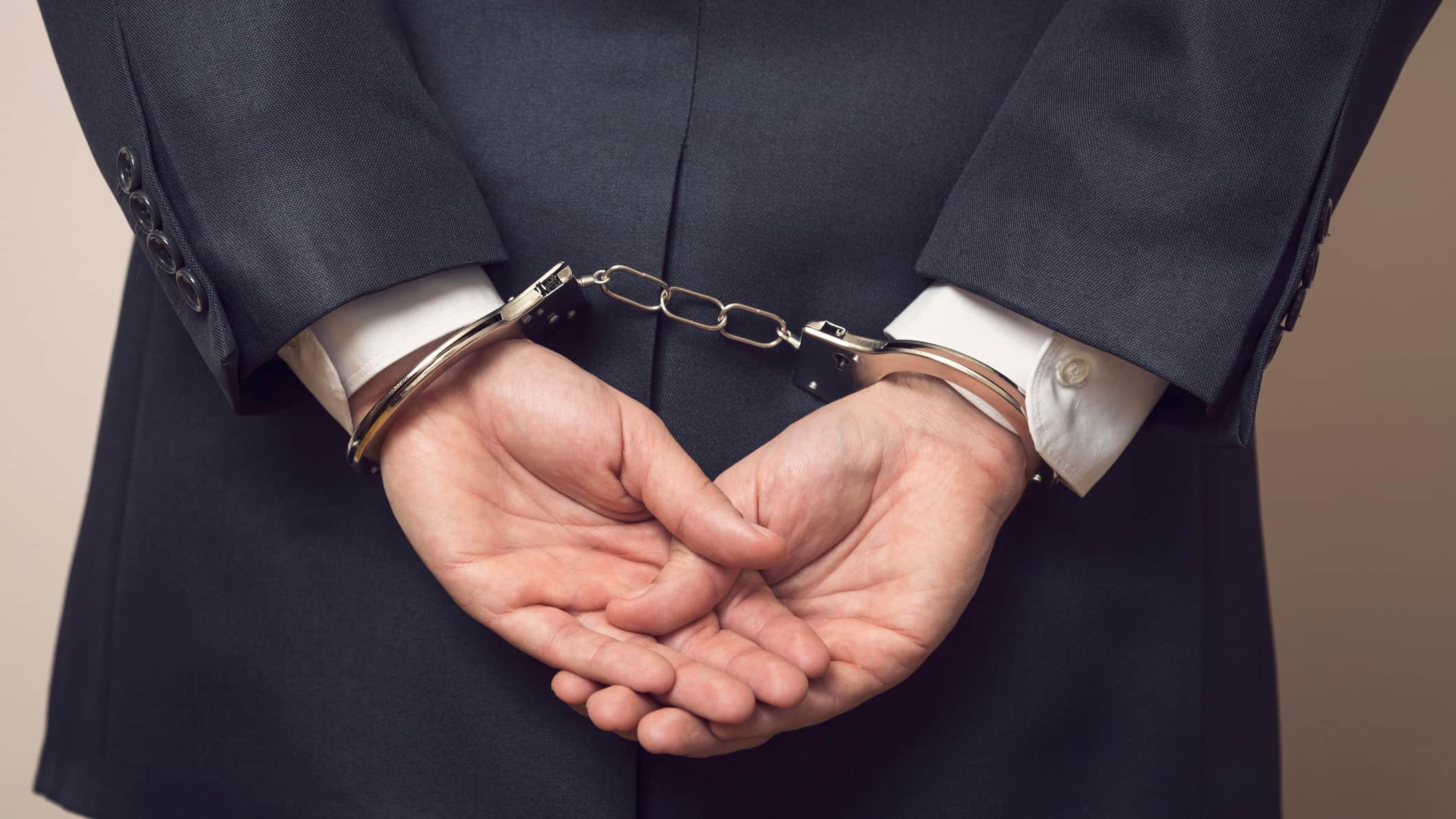 business man with hands handcuffed behind back